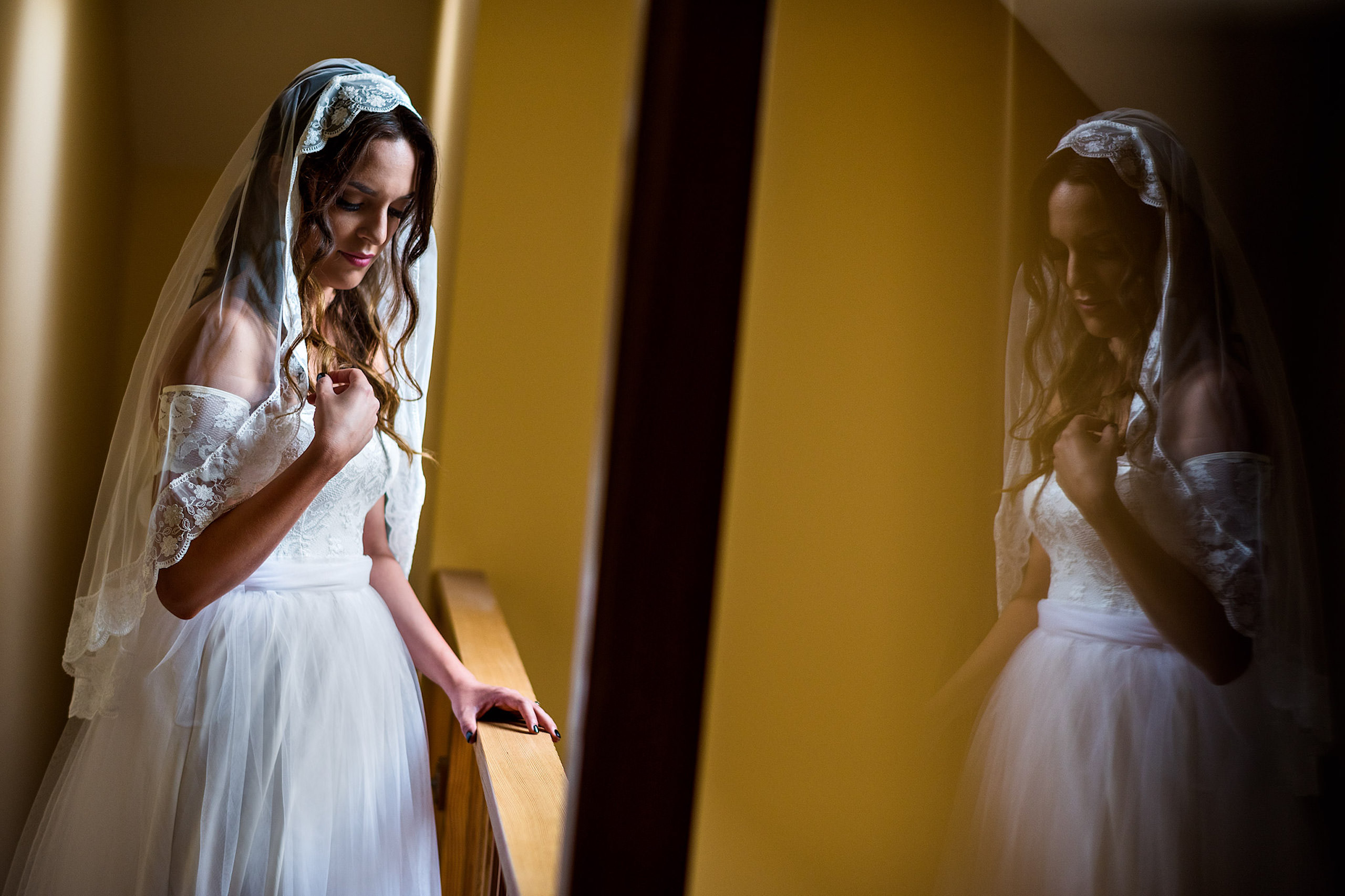 a bride posing in front of a hall way - a room of bridesmaids getting ready - Qualicum Wedding Photographer