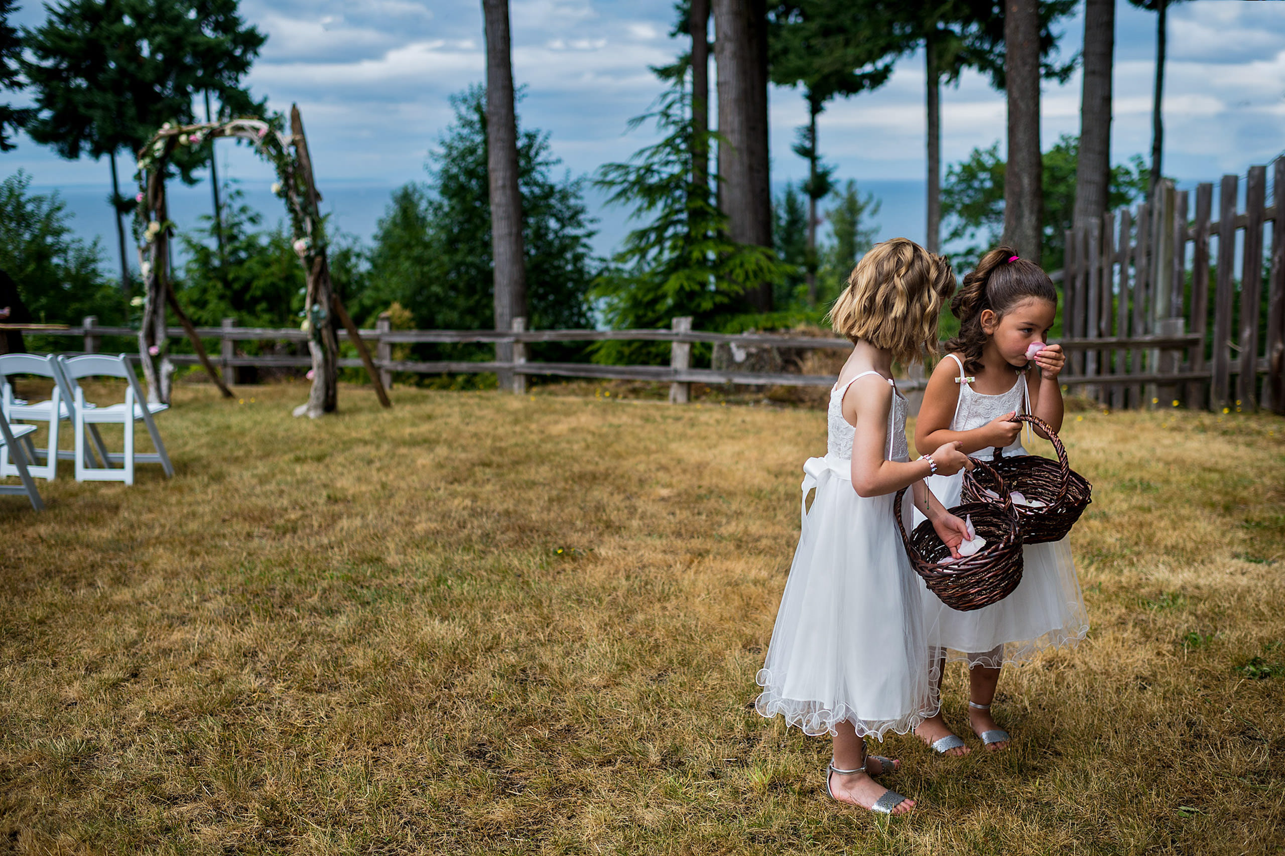 Two little girls standing on grass in front of a lake in BC - Qualicum Wedding Photographer