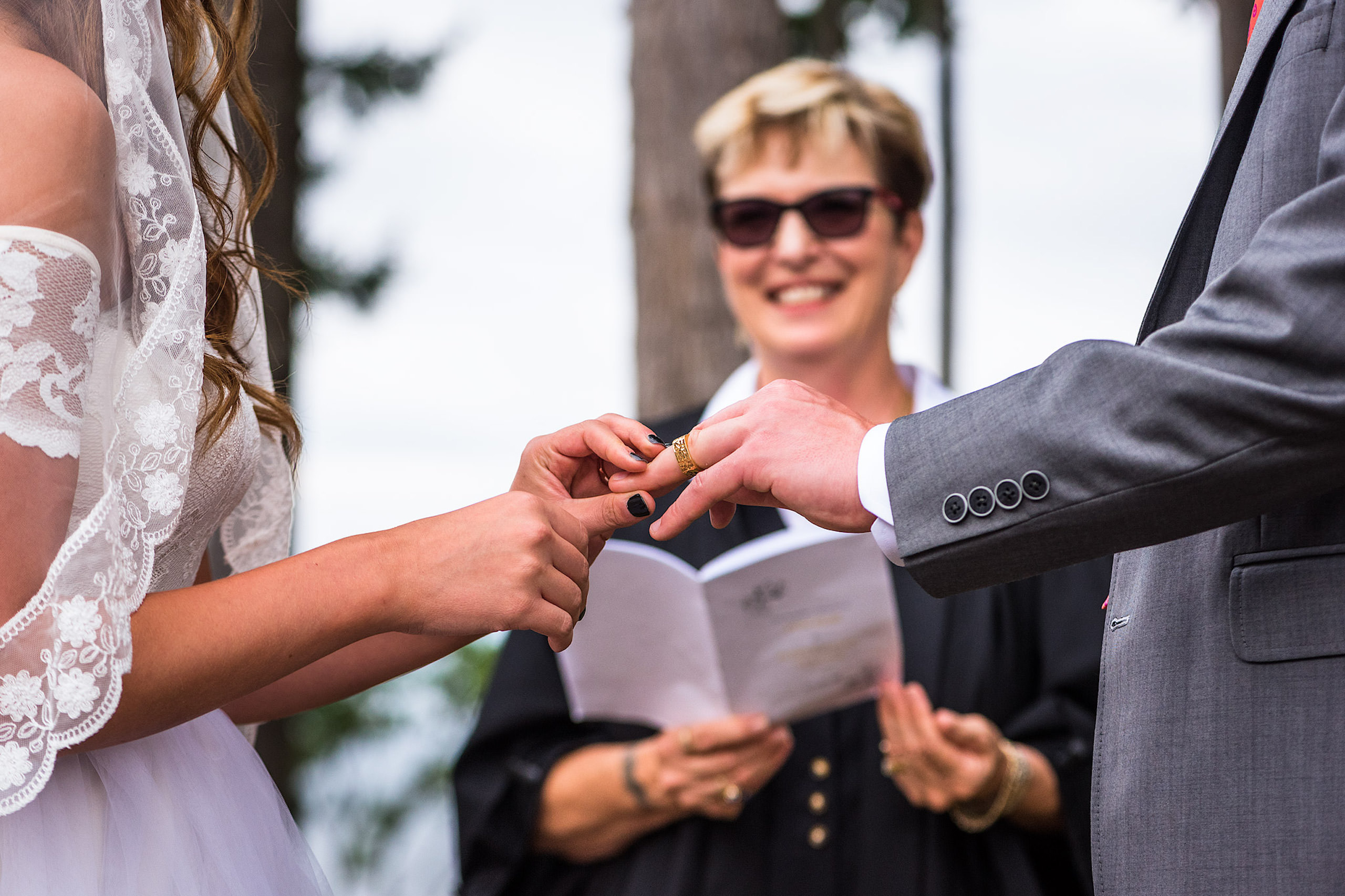 A bride putting on a ring on a grooms finger - Qualicum Wedding Photographer