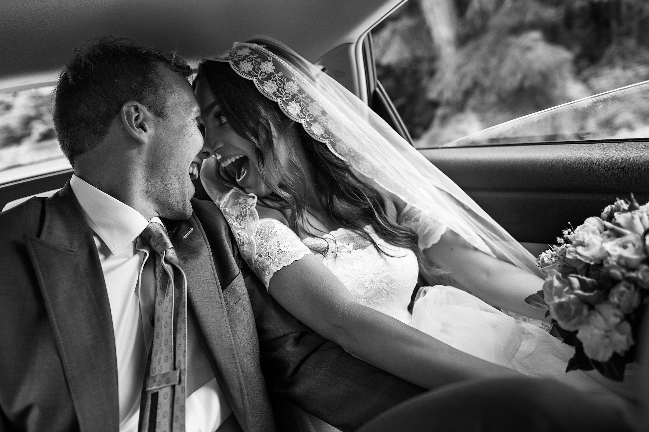A bride and groom sitting in the back seat of a car with big smiles - Qualicum Wedding Photographer