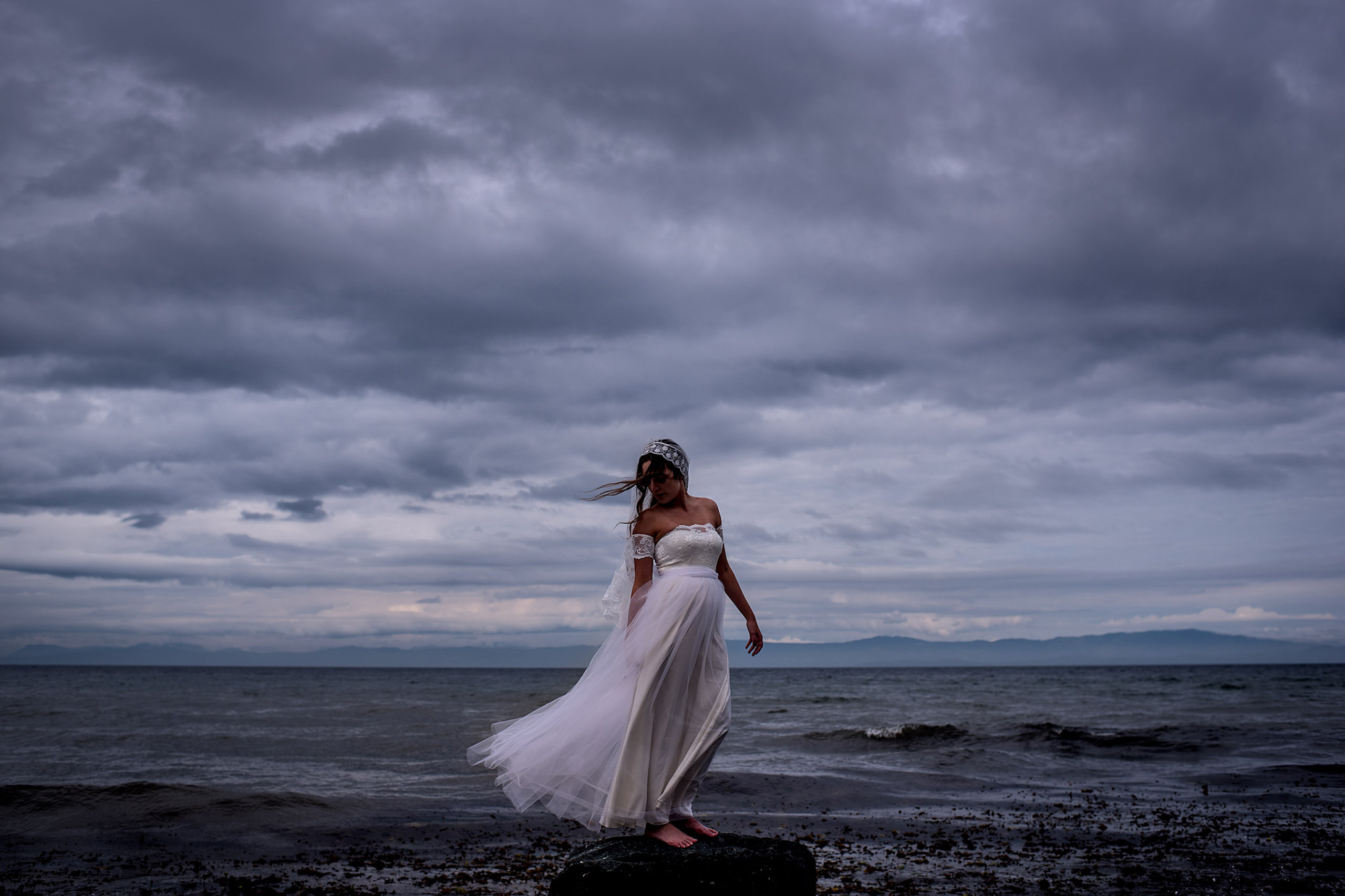 A beautiful bride standing on a rock for a portrait in BC - Qualicum Wedding Photographer
