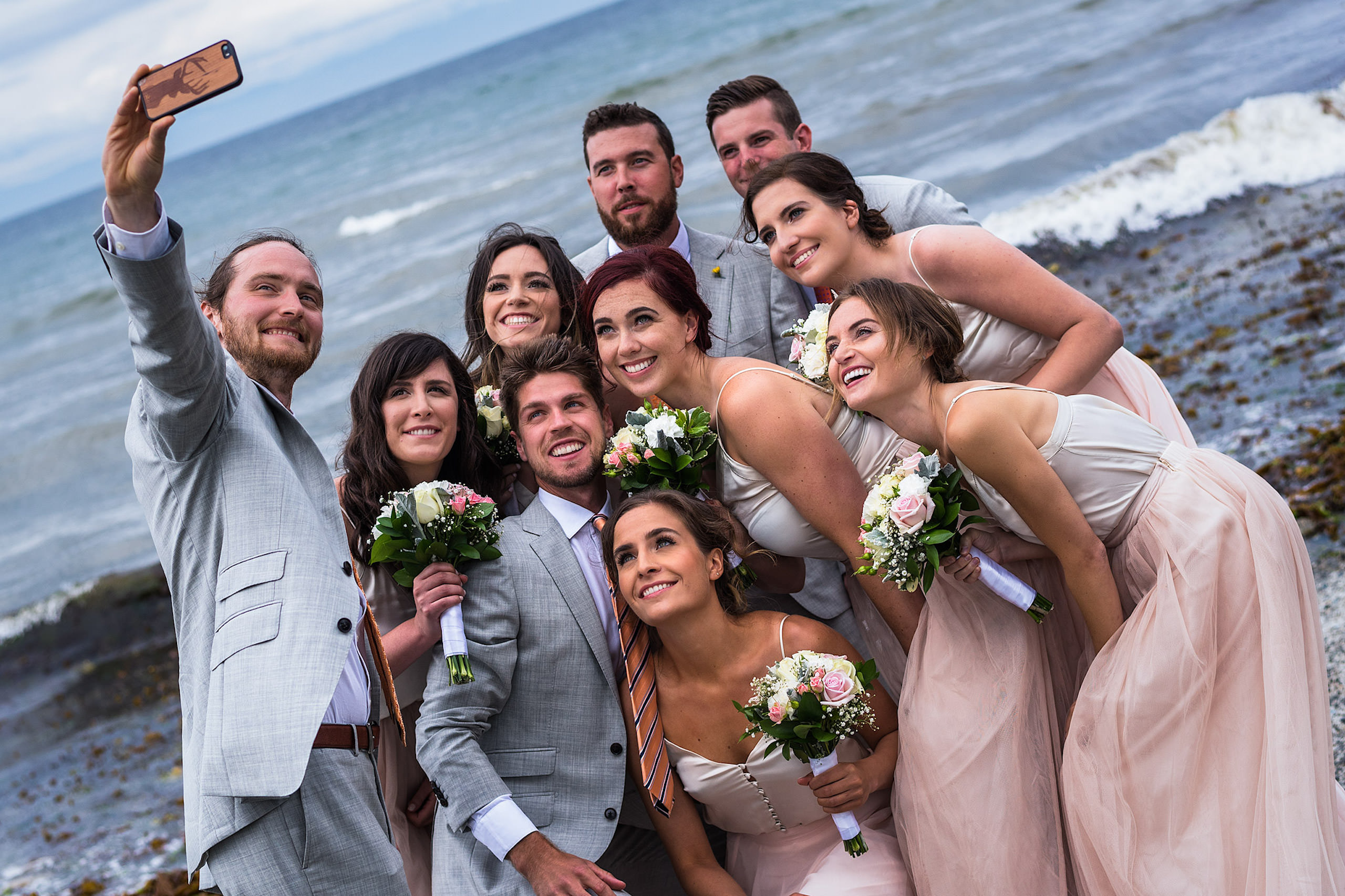 A wedding party posing for a photograph on a beach in BC - Qualicum Wedding Photographer