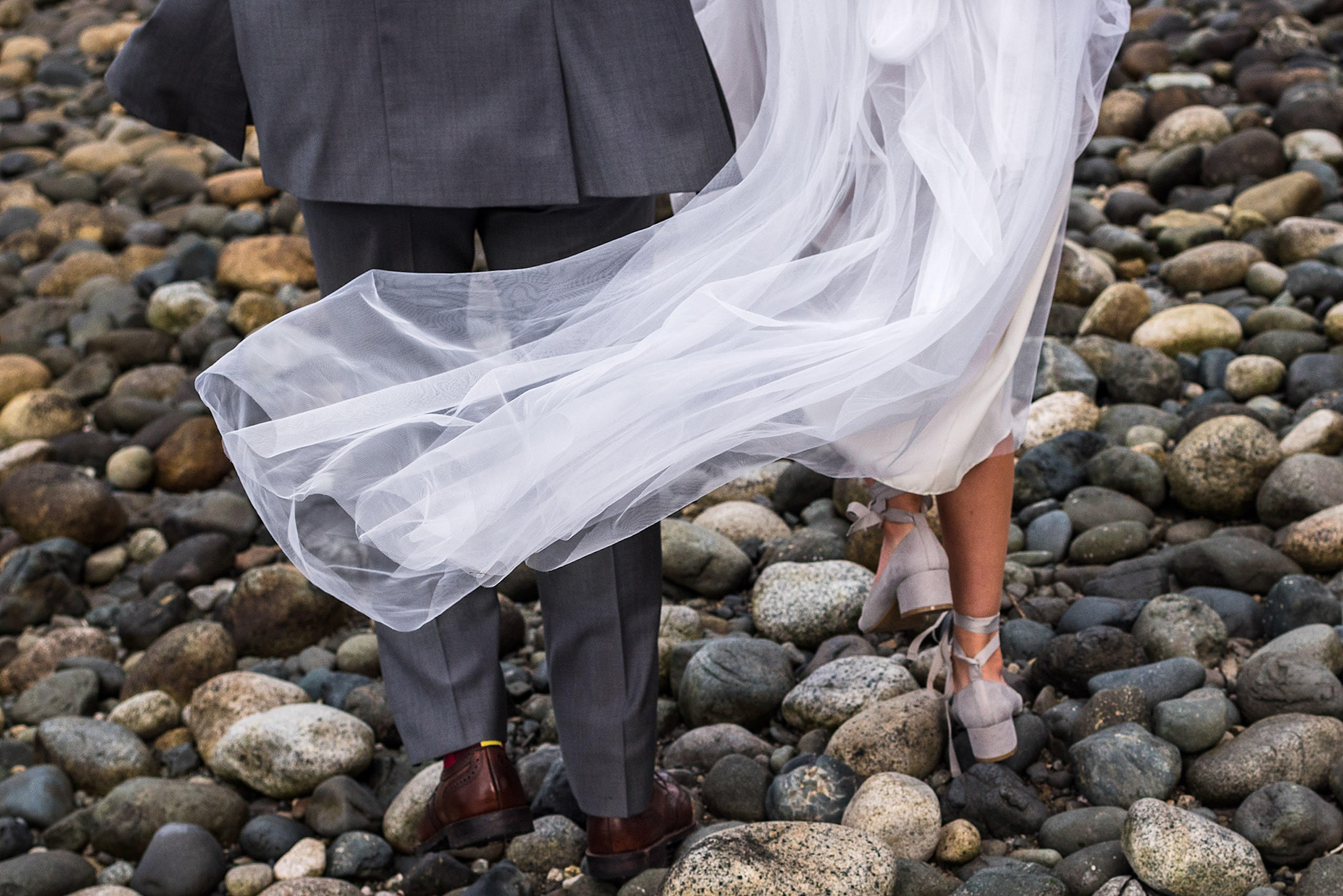 A close up of the back of a bride and groom walking on a beach in BC - Qualicum Wedding Photographer