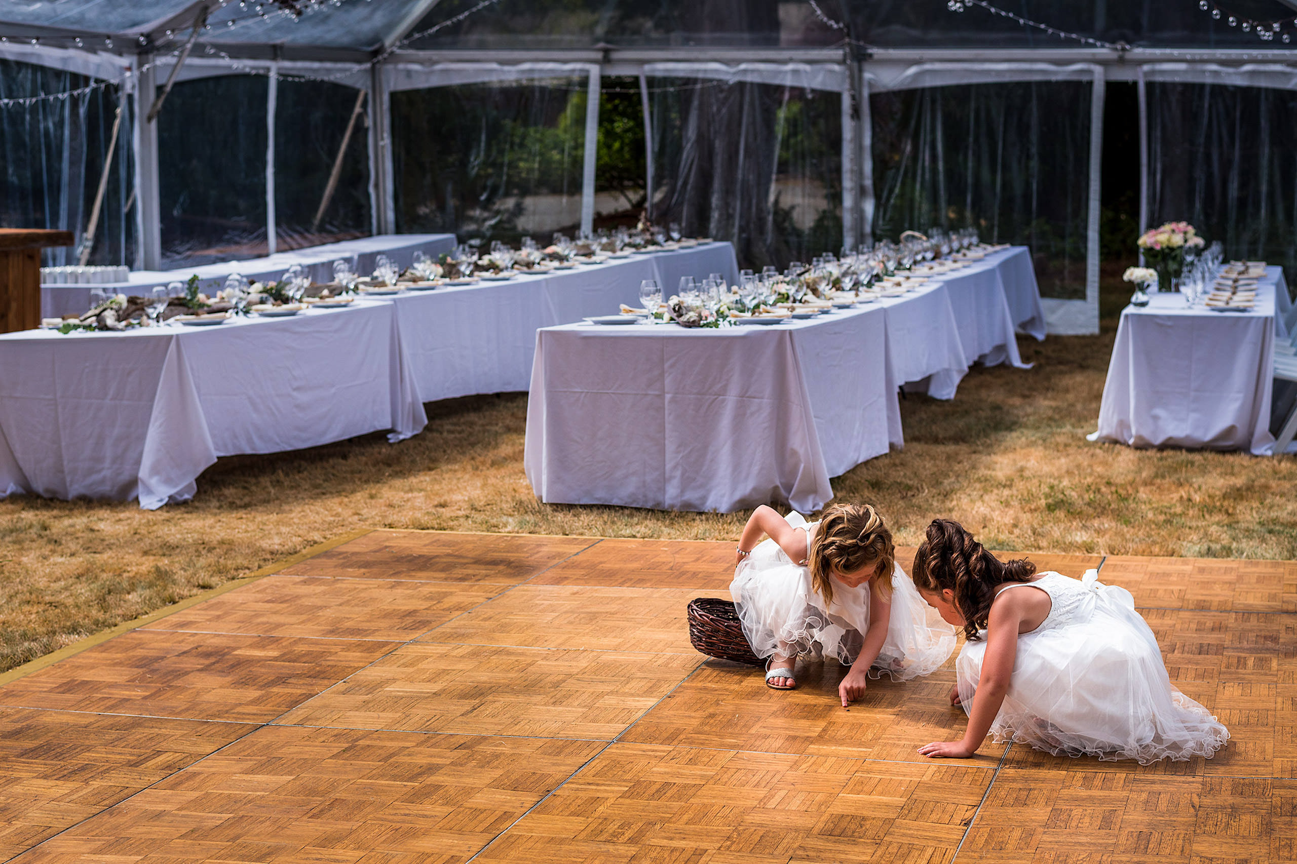 Two little flower girls looking at a bug on the dance floor - Qualicum Wedding Photographer
