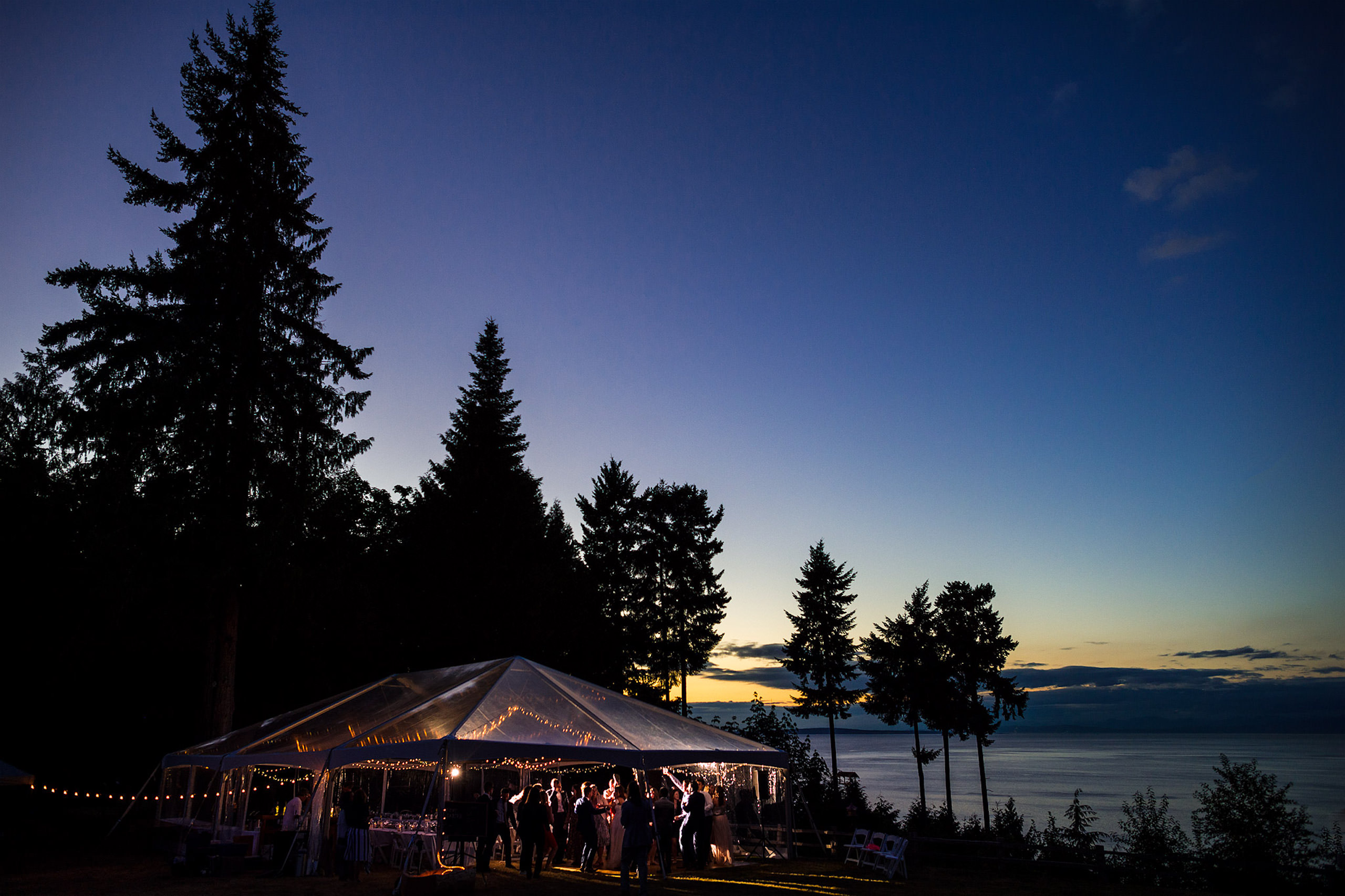 Wide angle photograph of a tent at a wedding reception in low light - Qualicum Wedding Photographer