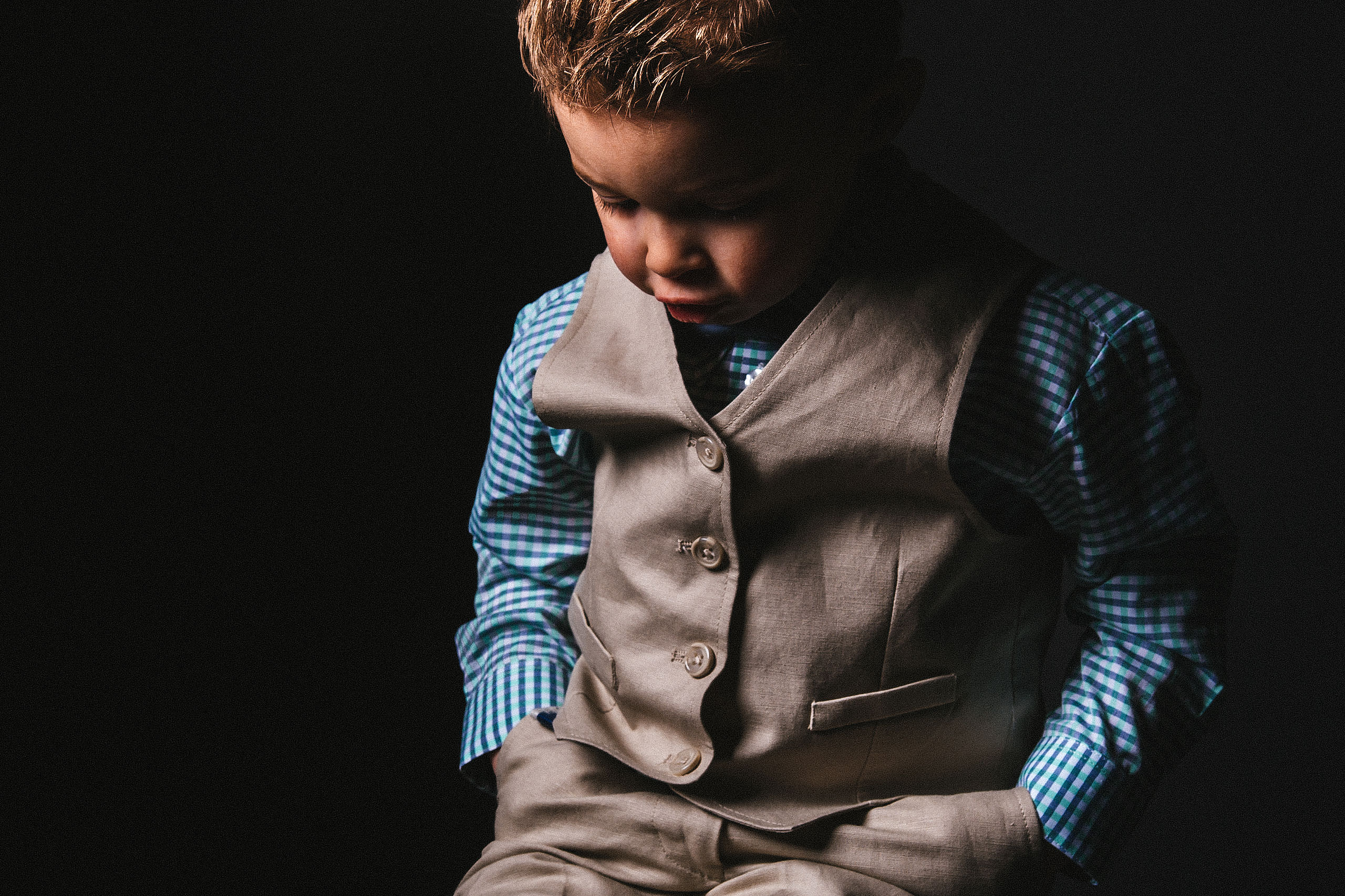 a young boy with his hands in his pockets looking down by top family portrait photographer sean leblanc
