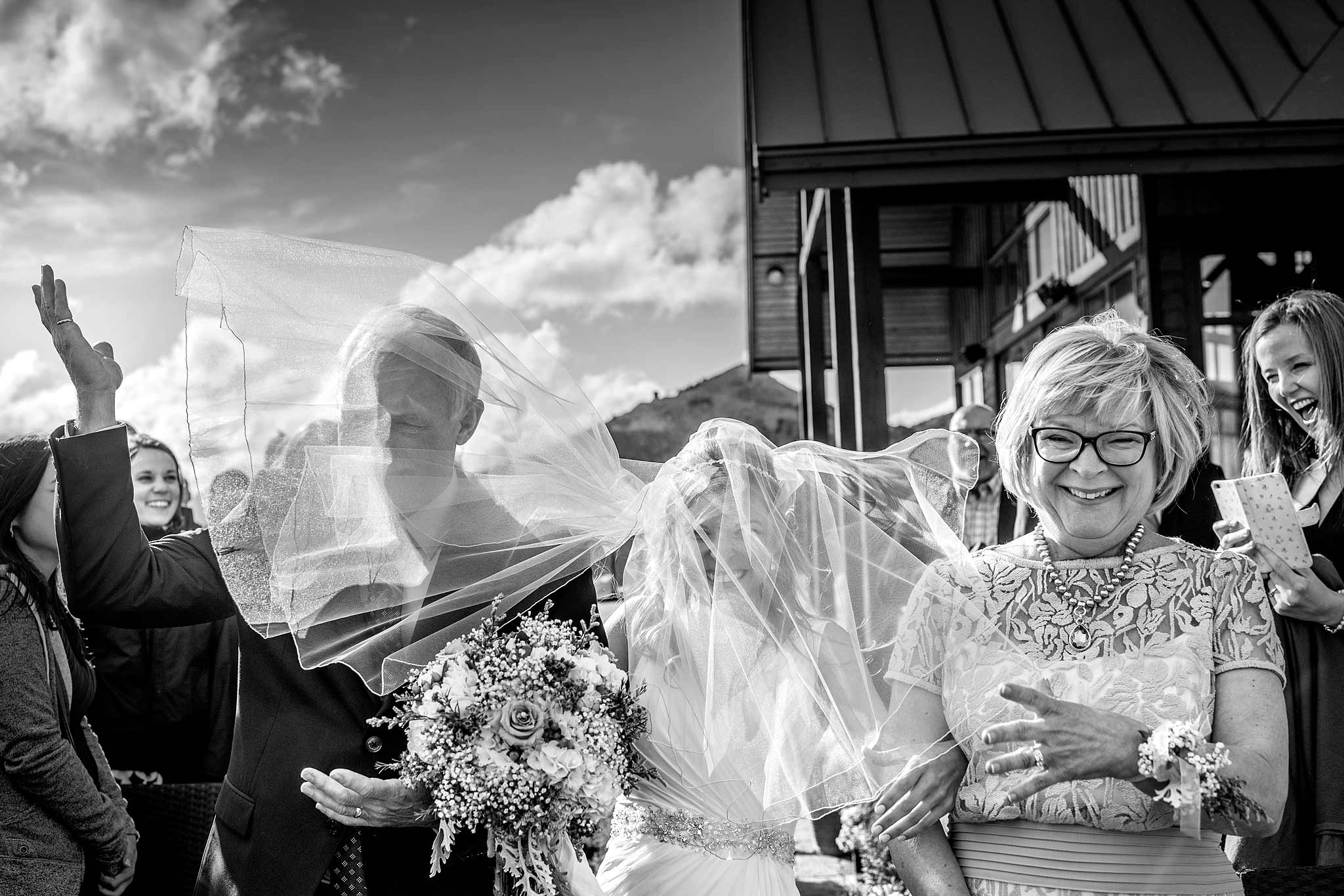 a bride's parents walking her down the aisle with her veil covering all three of them by kicking horse wedding photographers