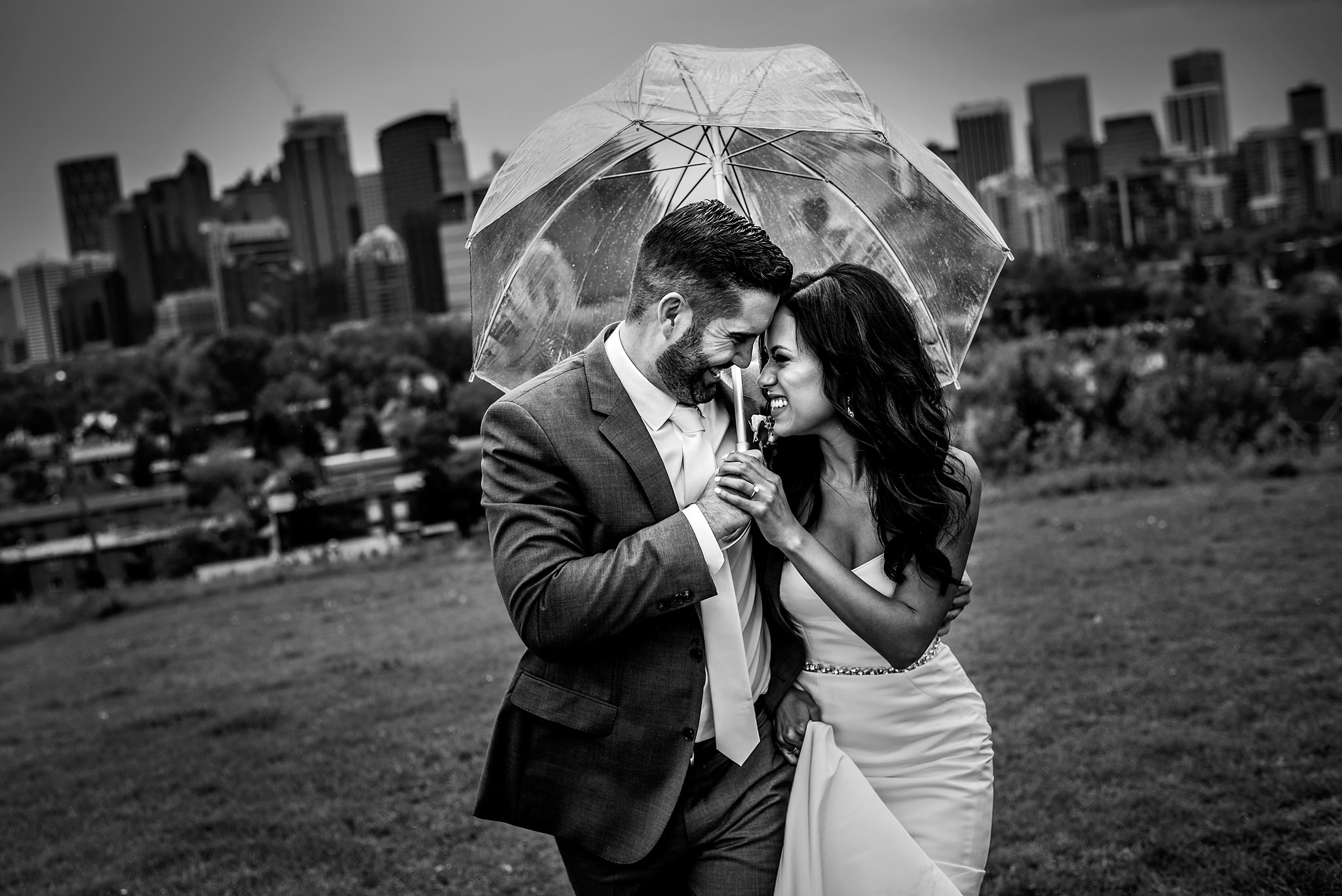 bride and groom walking up a hill together holding an umbrella with the downtown city skyline in the background