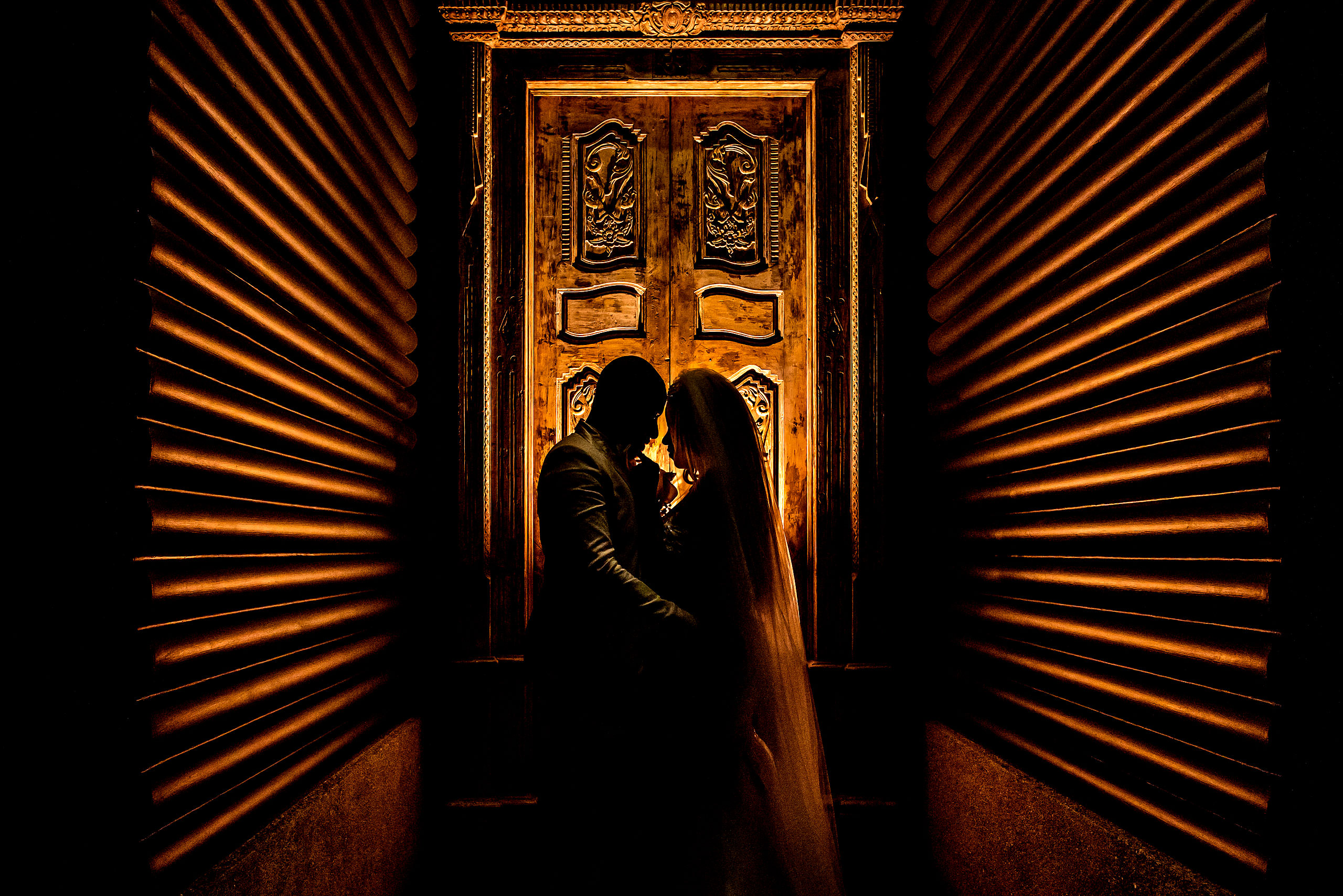 bride and groom embracing silhouetted against a carved door