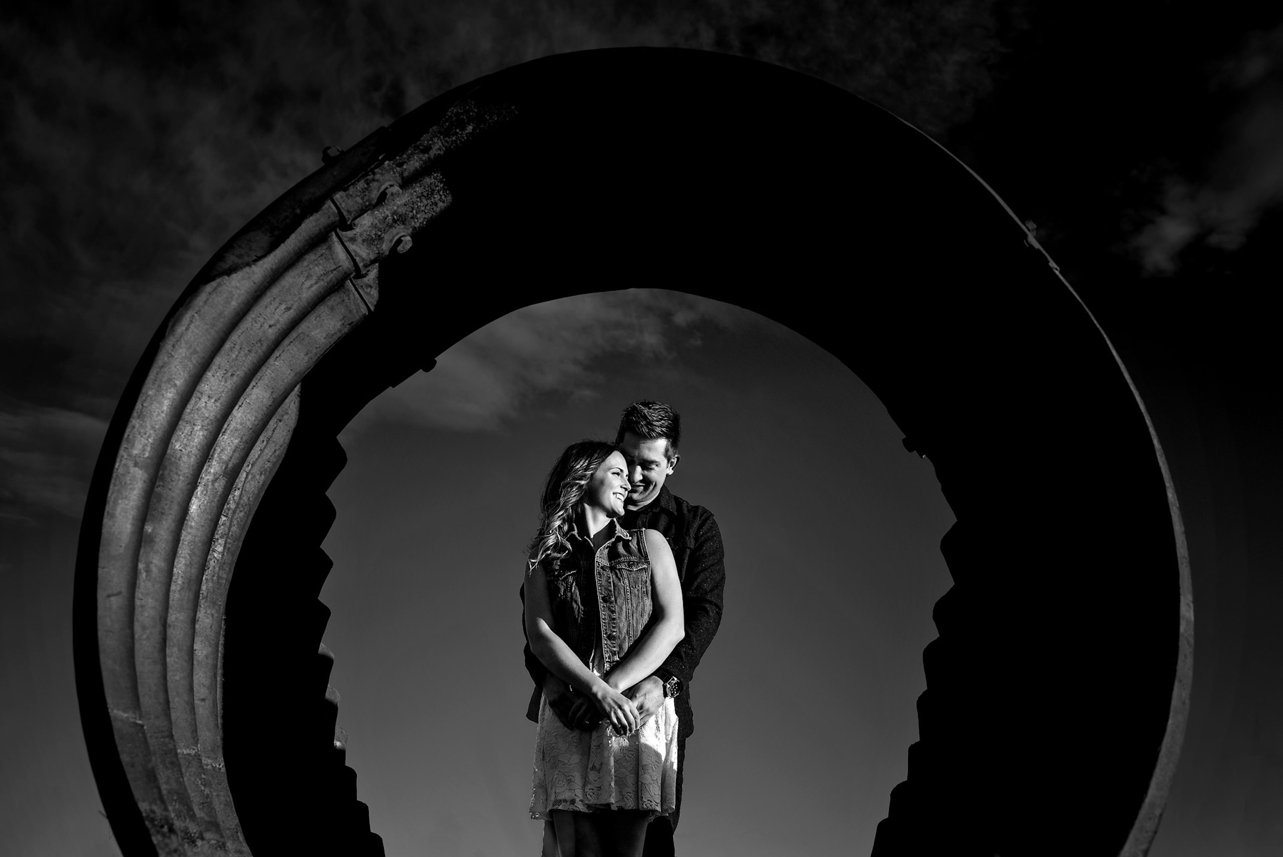 a couple standing behind a culvert by top calgary engagement photographer sean leblanc
