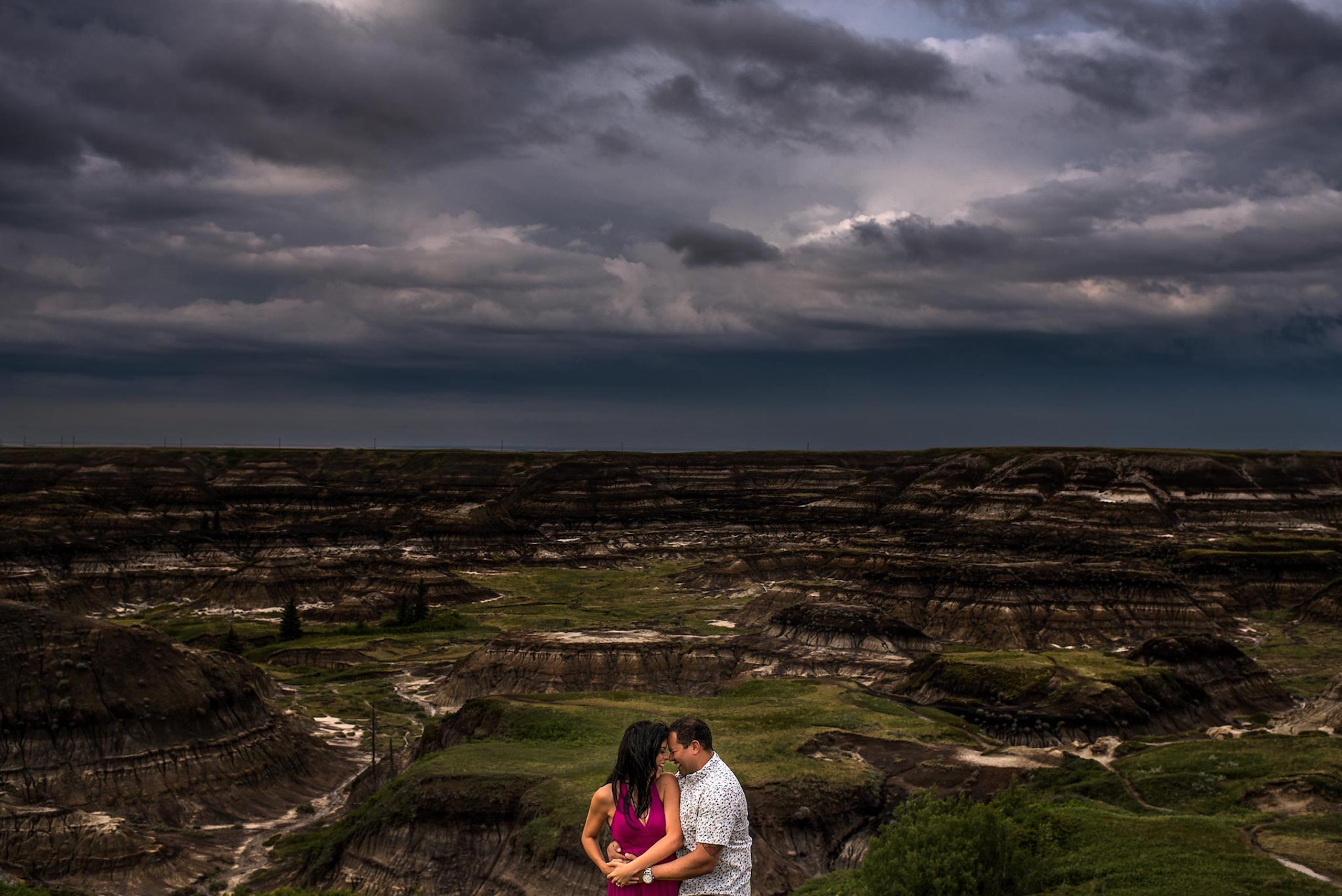 man and women embracing and smiling at each in front of a canyon by top calgary engagement photographer sean leblanc