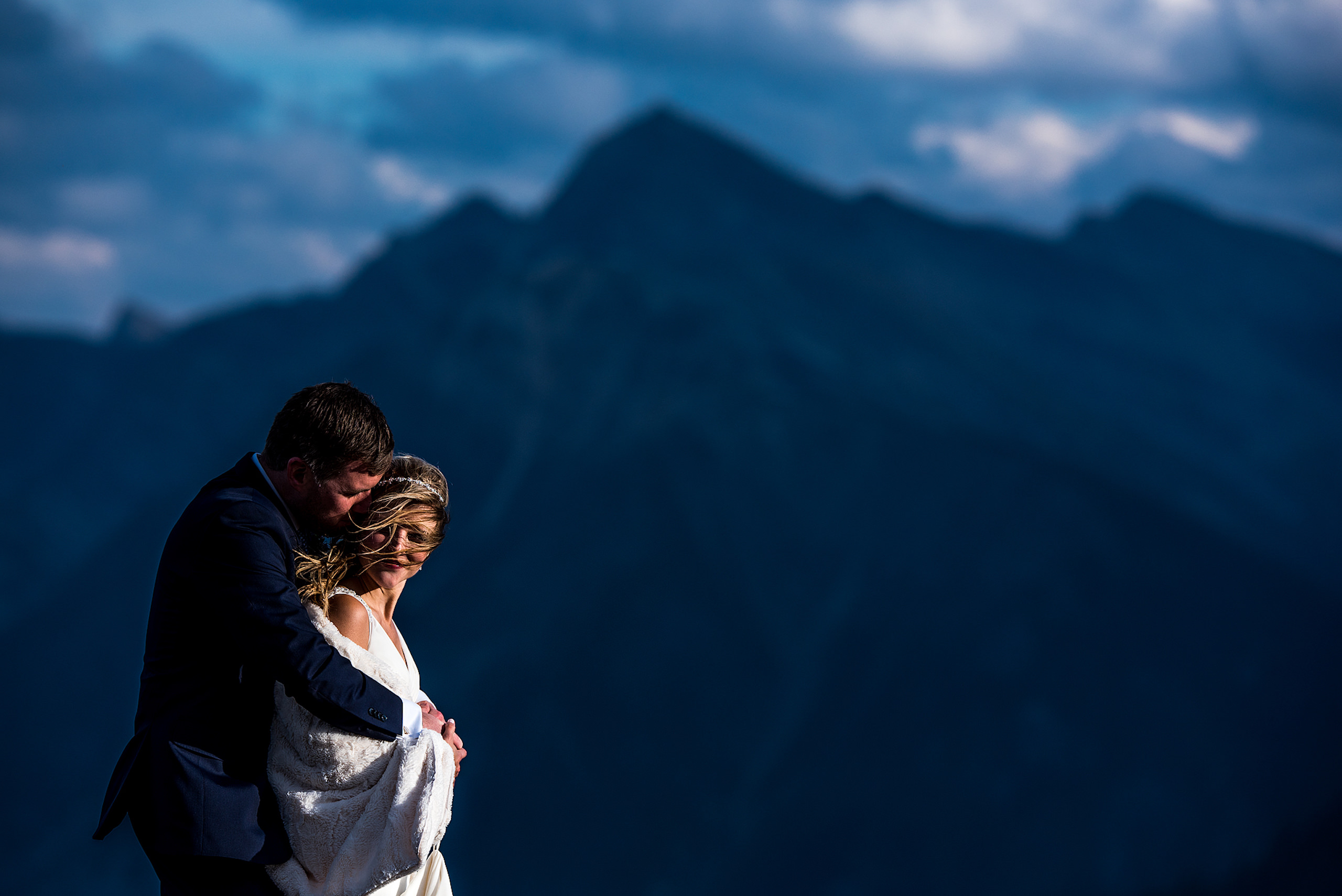 bride and groom embracing in front of a mountain at summer kicking horse wedding