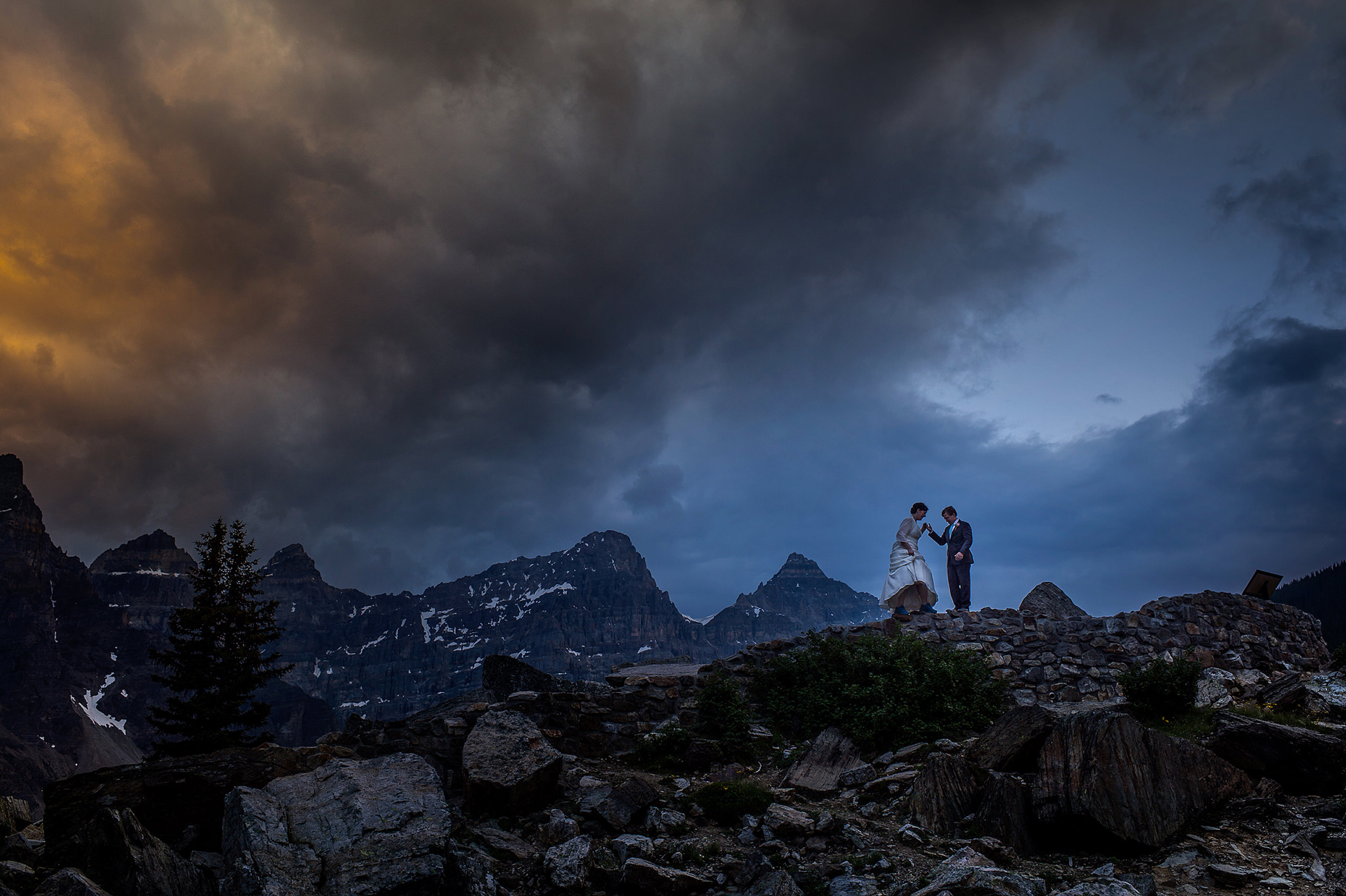 bride and groom standing on top of a mountain by lake Louise wedding photographer