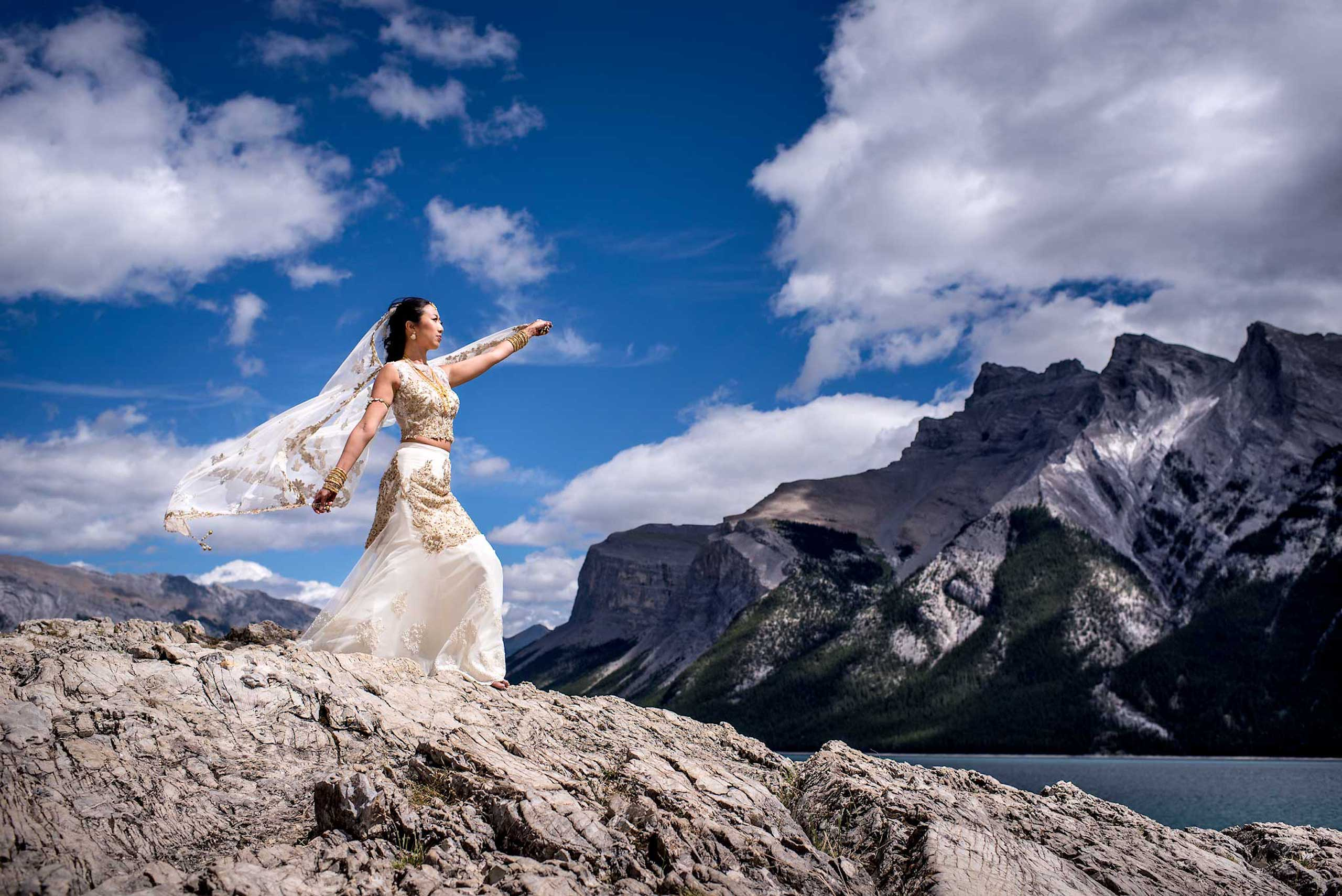 bride posing on a mountain in front of a lake by Banff wedding photographer