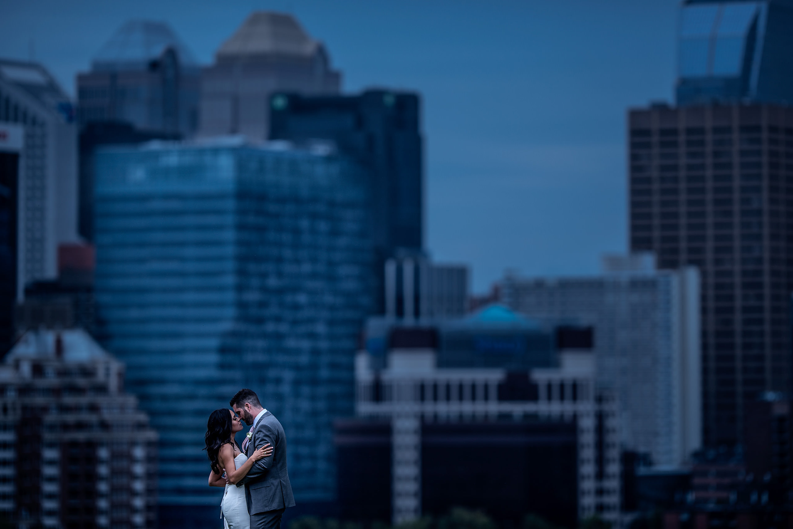 bride and groom about to kiss with the city skyline in the background