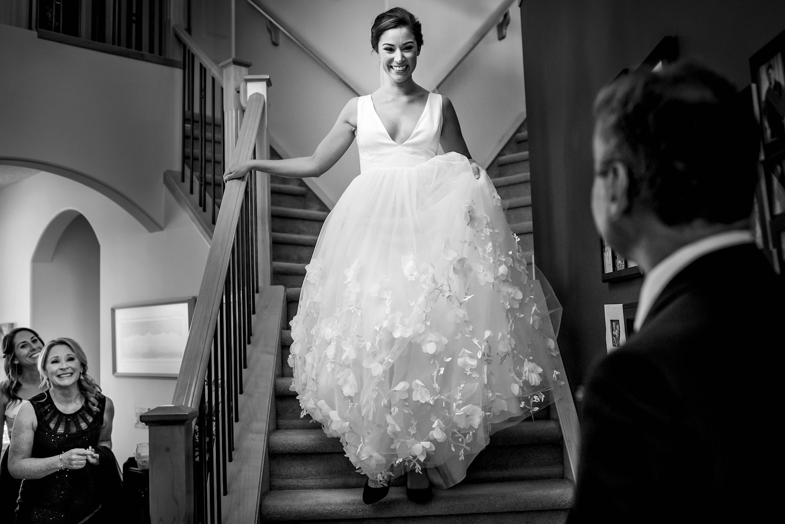 a bride walking down stairs seeing her dad for the first time on her wedding day by calgary wedding photographers