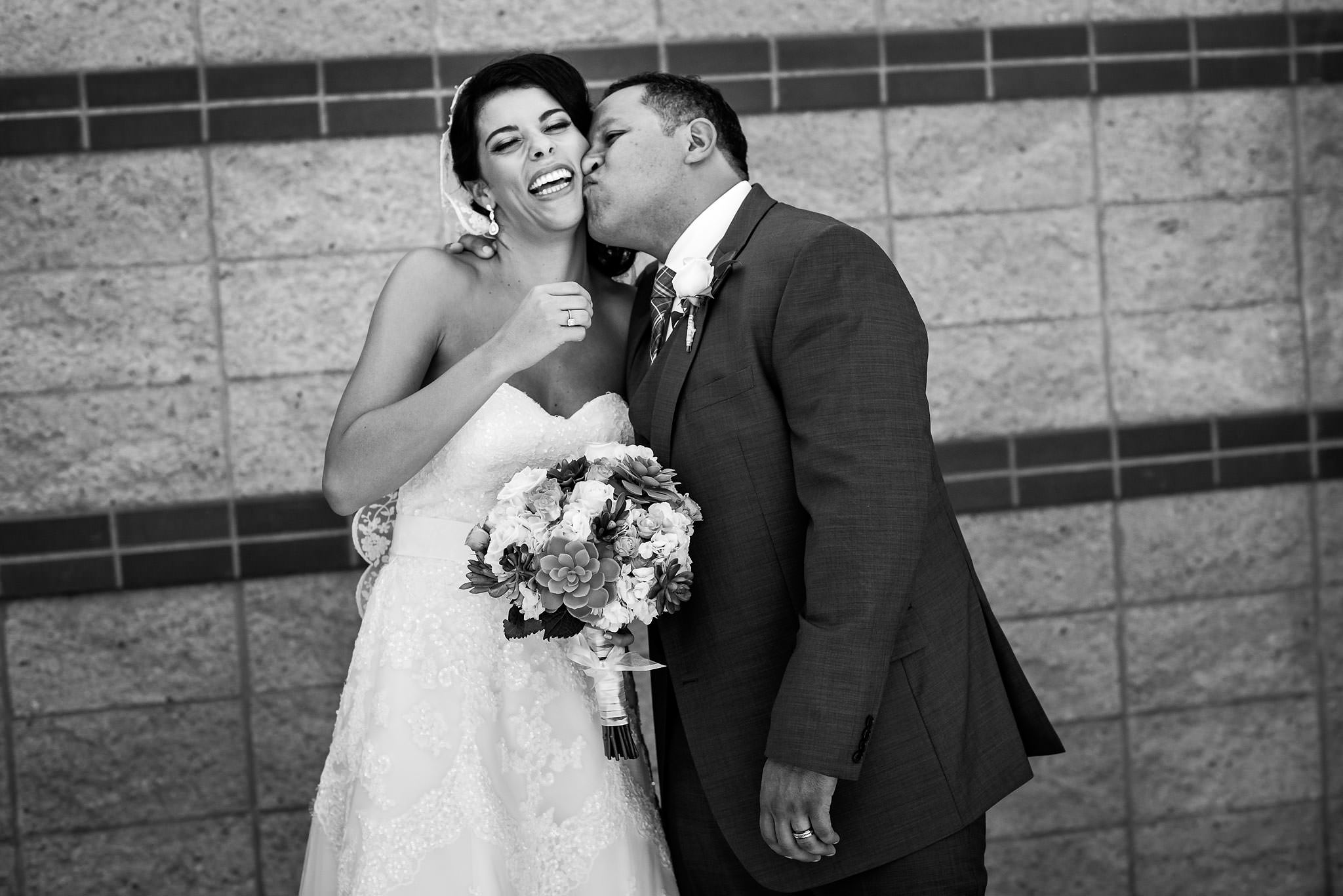 a groom kissing his bride in a funny way by Edmonton wedding photographers