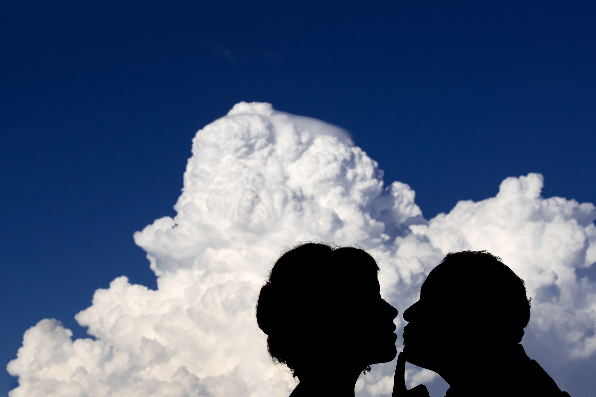 silhouette of a bride and groom about to kiss in front of a cloud by top calgary wedding photographer sean leblanc