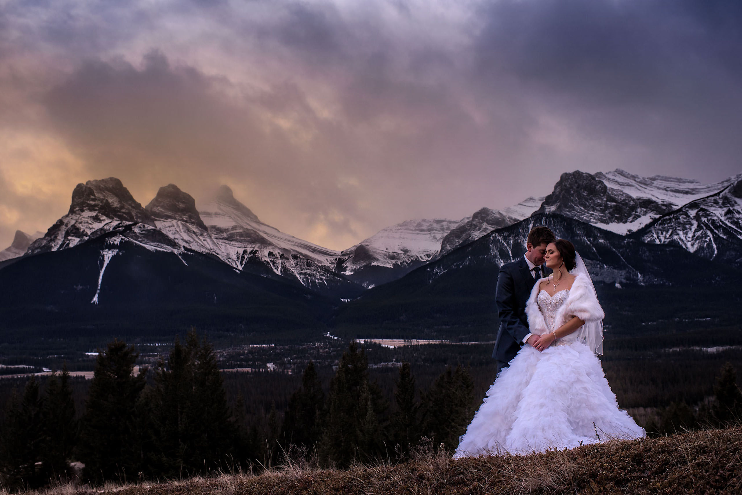 bride and groom embracing at the top of a mountain by Canmore wedding photographer