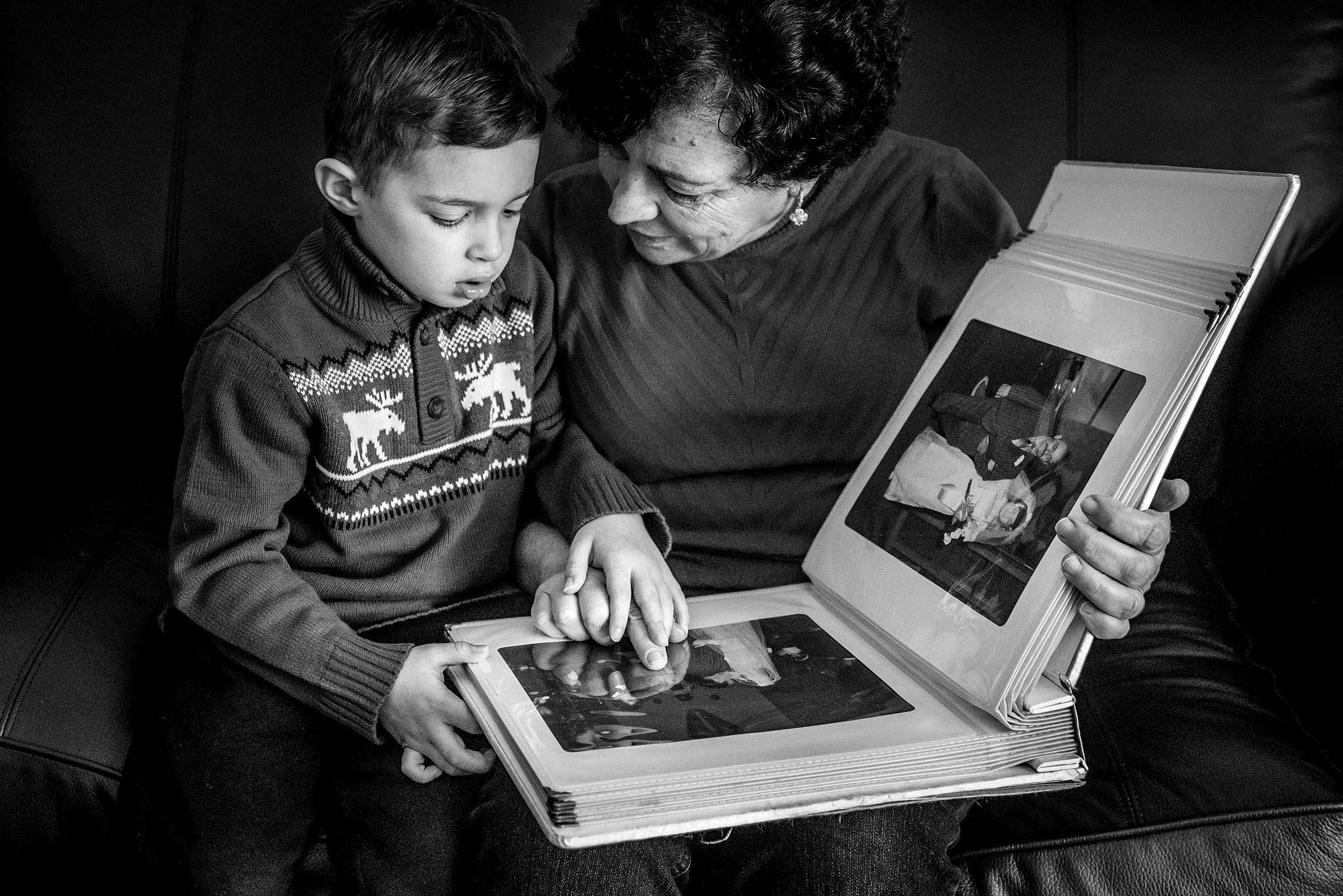 Grandma and boy looking through her old wedding album while sitting on a sofa top wedding photographer sean leblanc