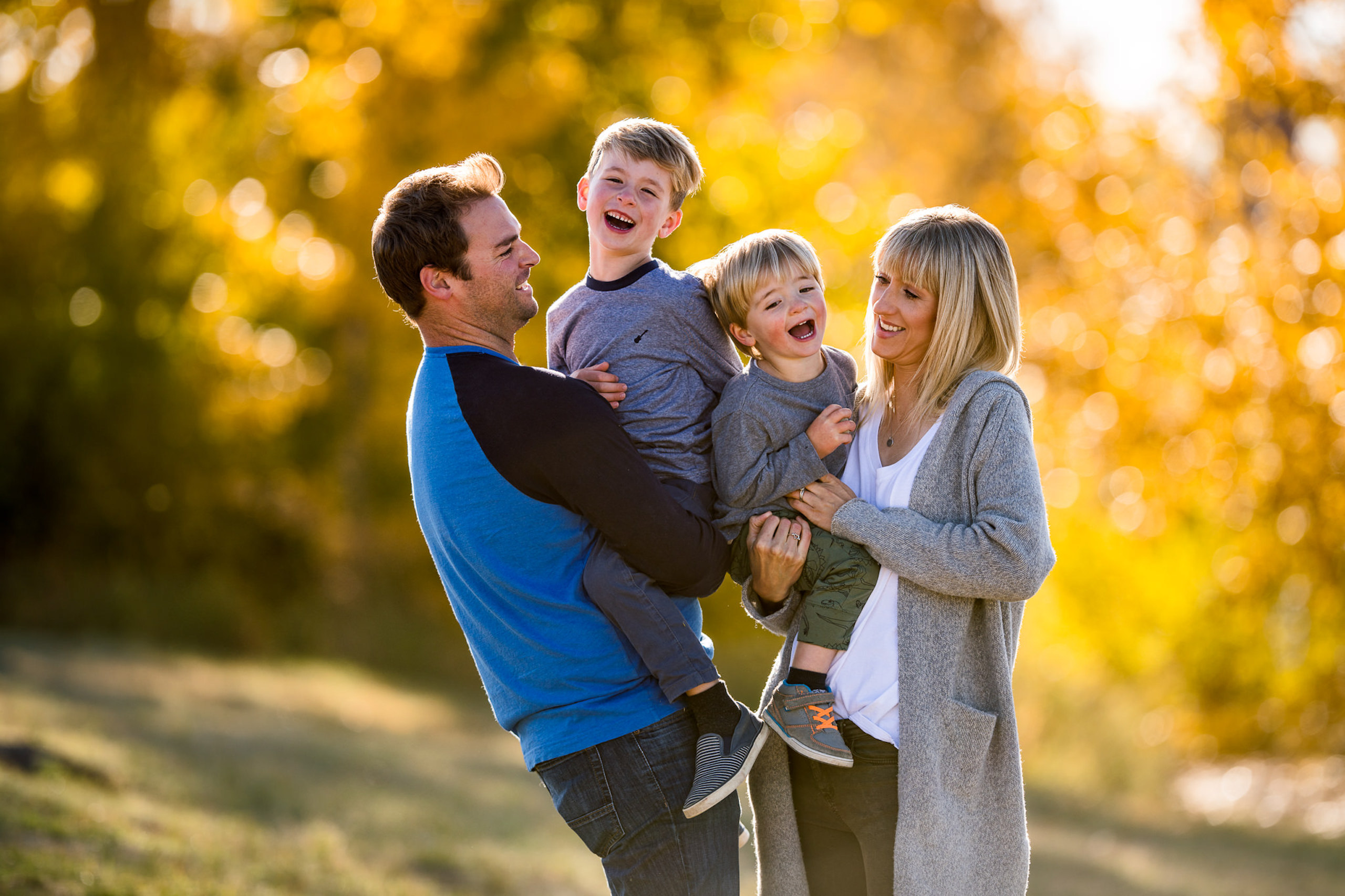 family of four in the park all smiling at reaching with yellow trees in the background