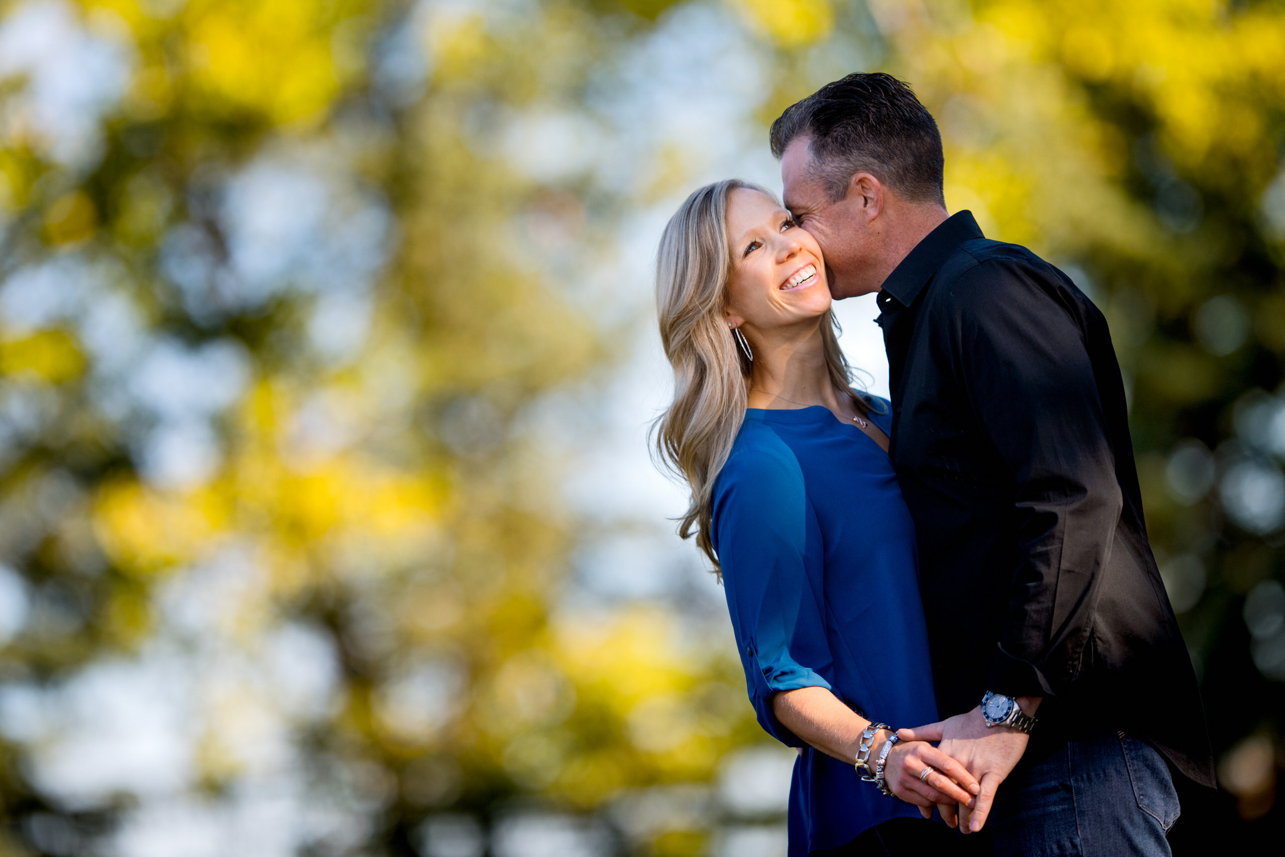 a married couple embracing in front of yellow coloured trees by top family portrait photographer sean leblanc