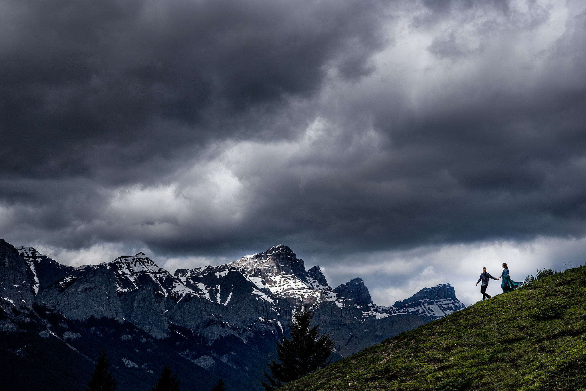 a couple walking down the side of a mountain by top calgary engagement photographer sean leblanc