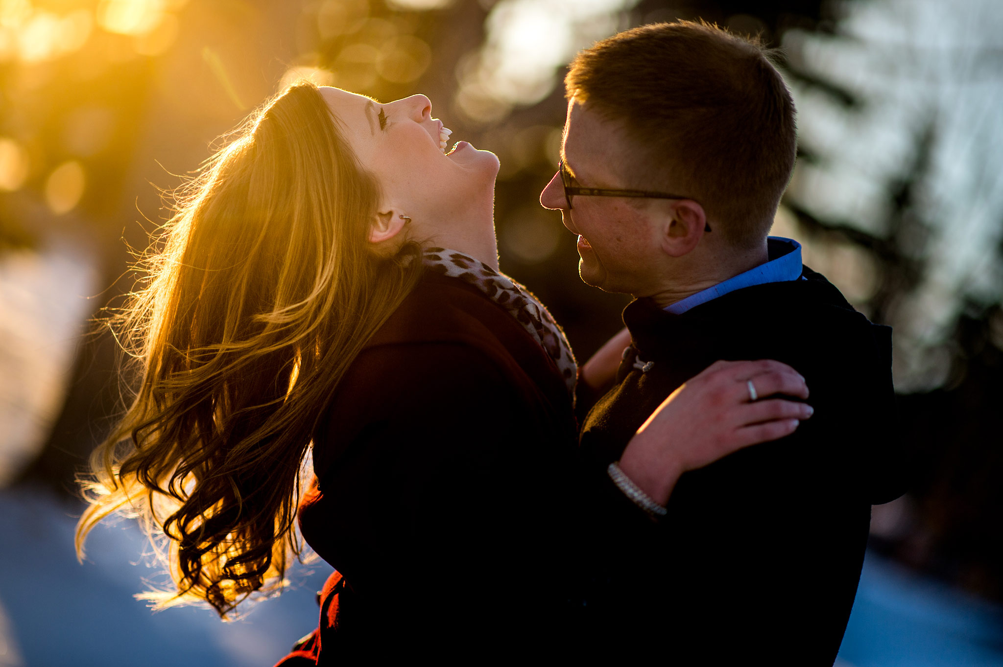 a man trying to kiss his fiancé by top calgary engagement photographer sean leblanc