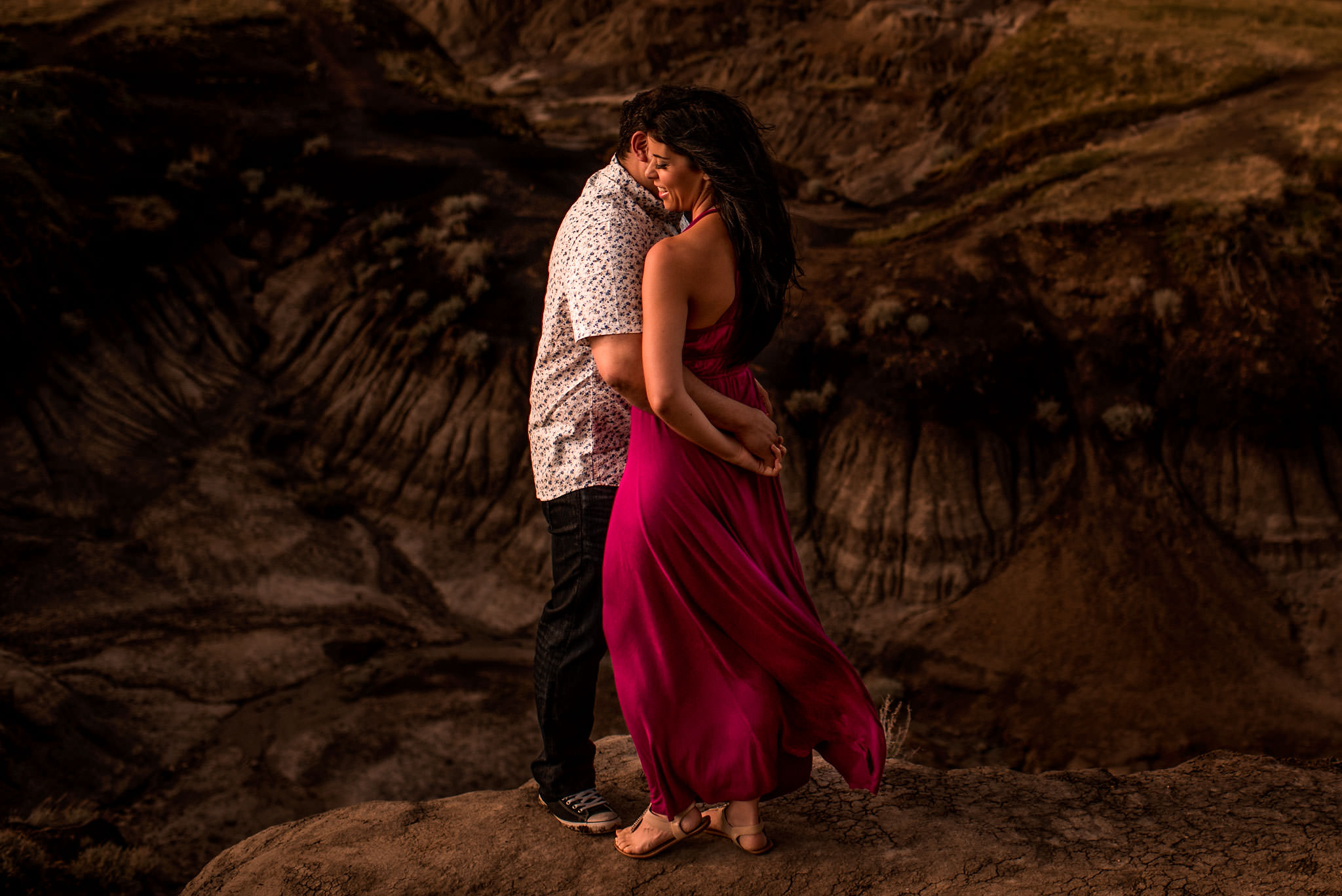 a women wearing a red dress hugging her fiancé in front of a canyon by top calgary engagement photographer sean leblanc