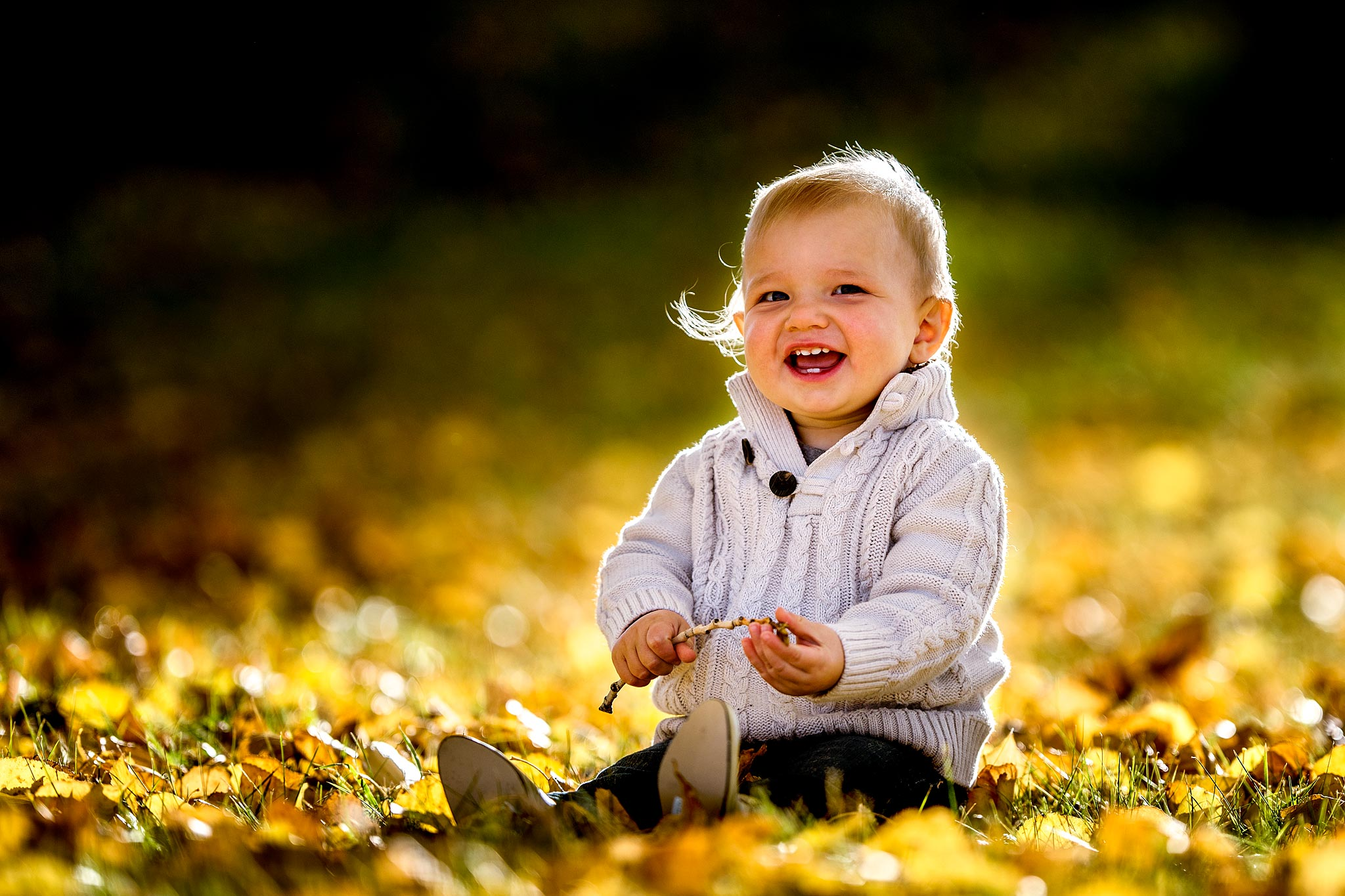 young boy sitting on the grass laughing and holding a stick