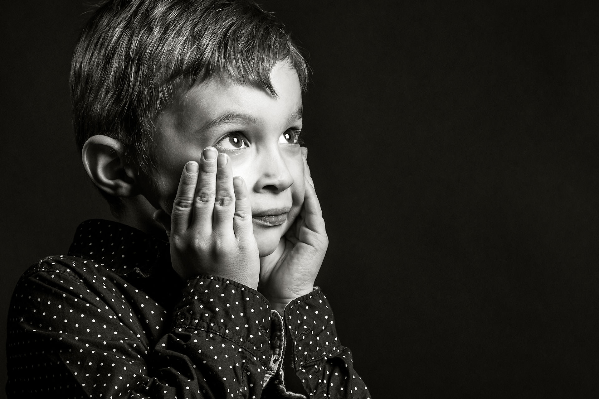 a young boy with his hands on either side of his face looking upward against a black backdrop by top family portrait photographer sean leblanc