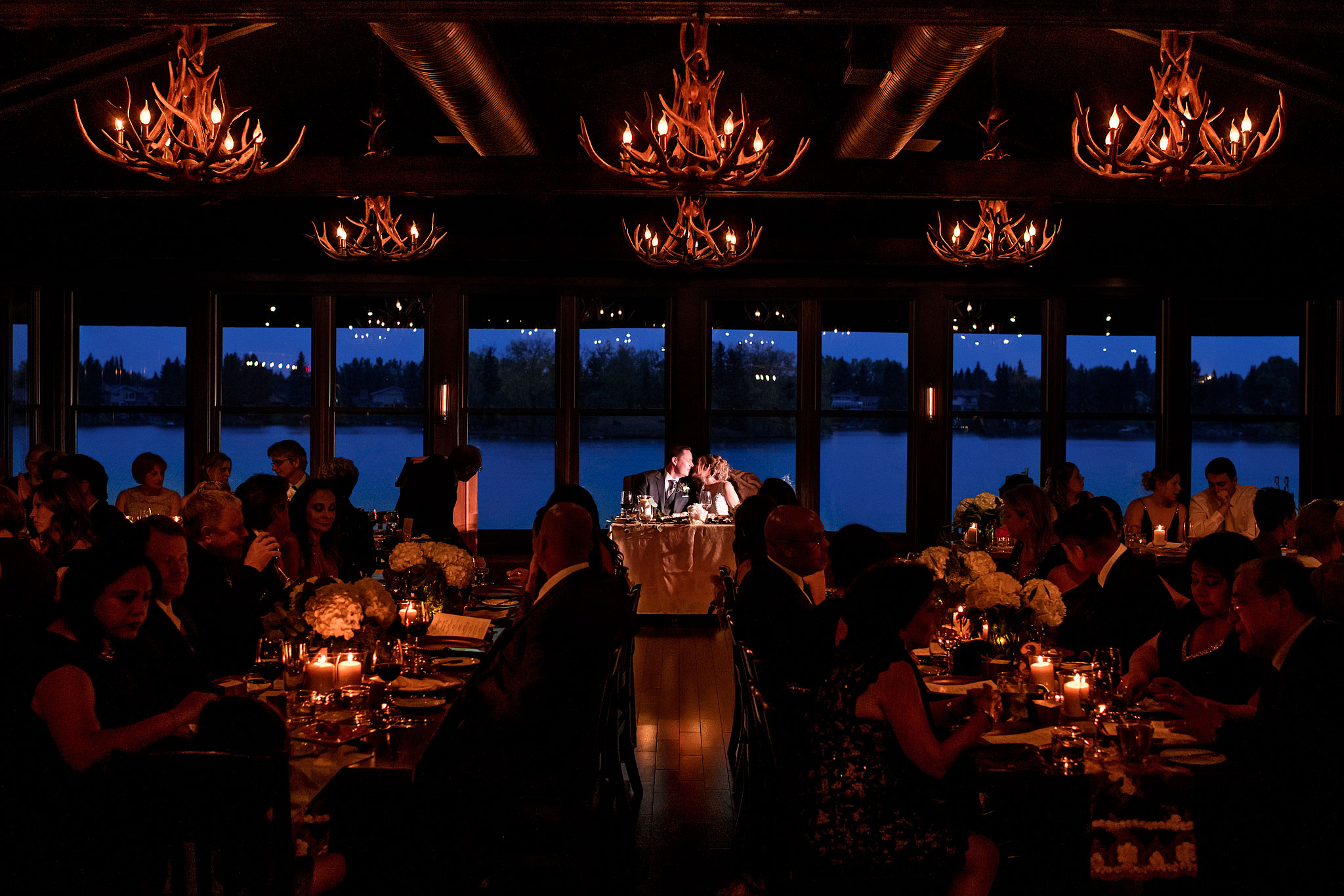 a bride and groom kissing at the head table during their wedding reception by calgary wedding photographers