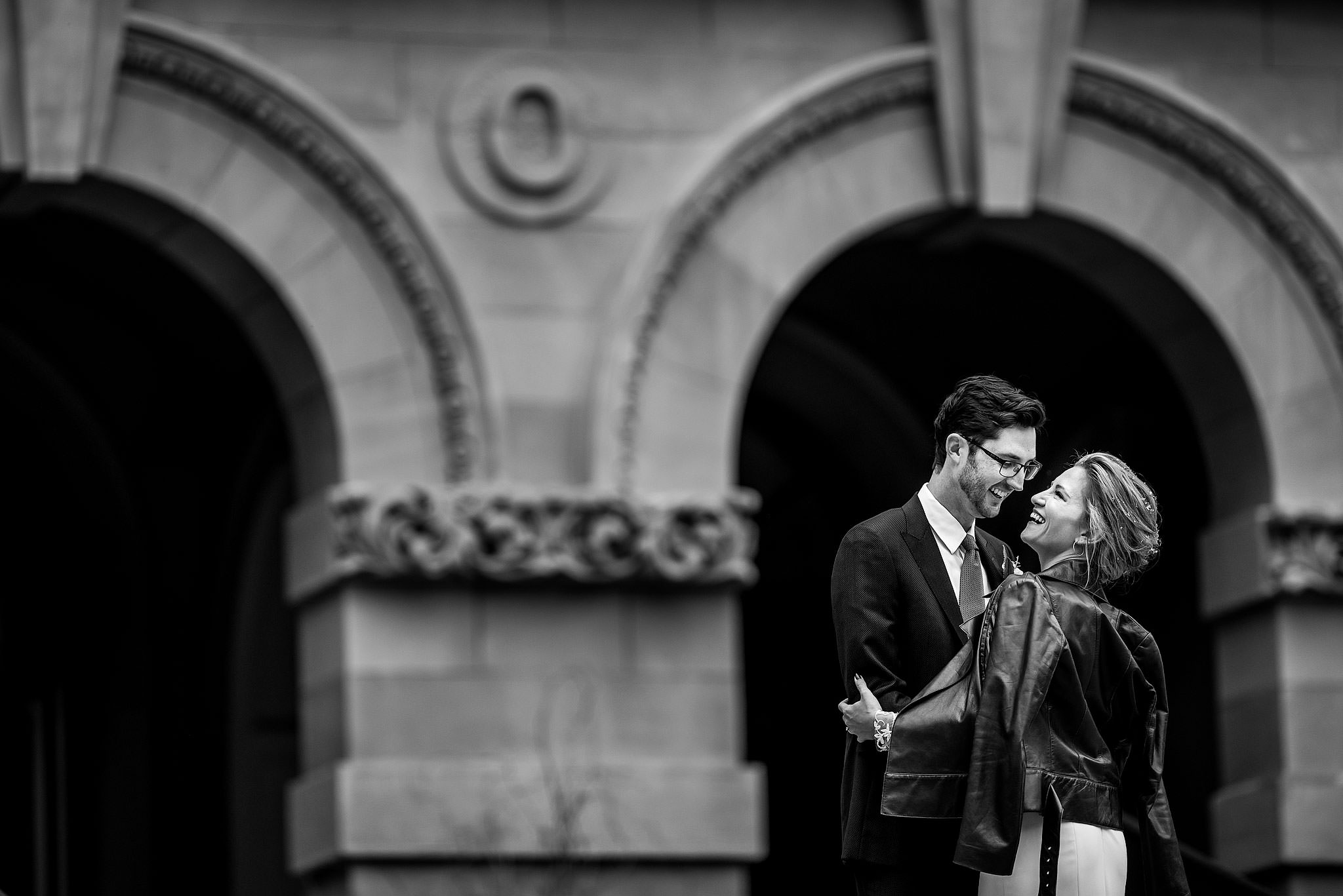 bride and groom embrace in front of a building by calgary wedding photographer sean leblanc