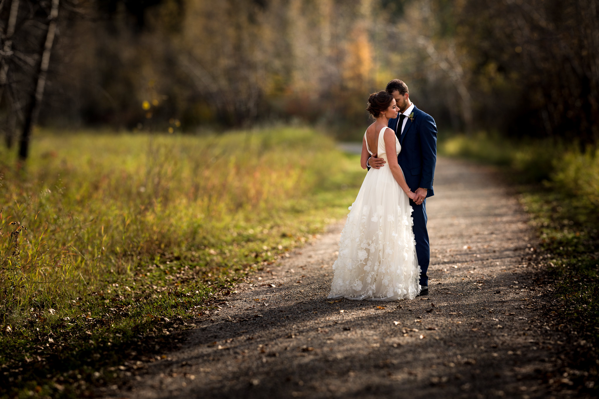 bride and groom embracing in a park by calgary wedding photographer sean leblanc