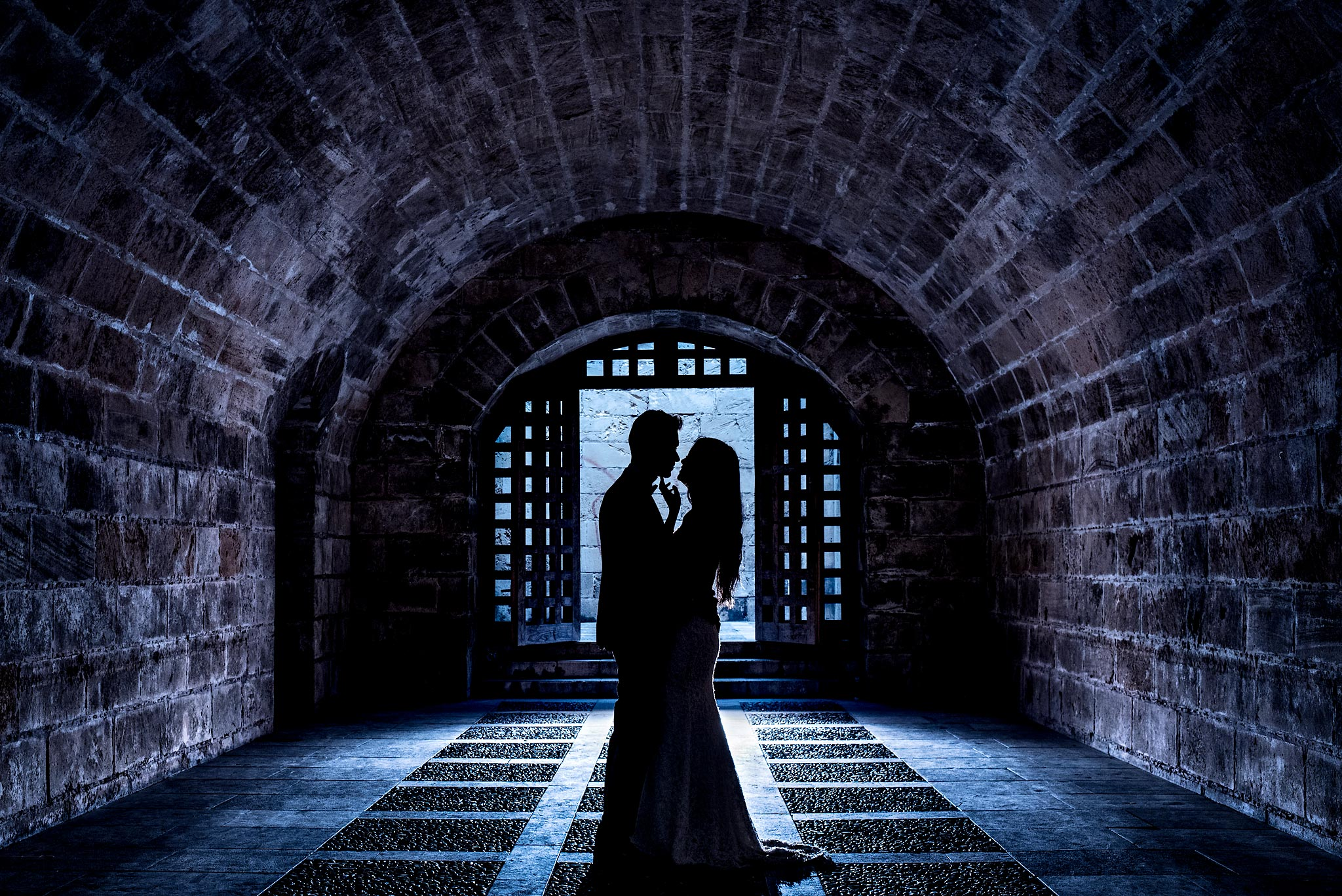 bride and groom silhouetted in a cave of a Spanish castle - Mallorca Wedding Photographer