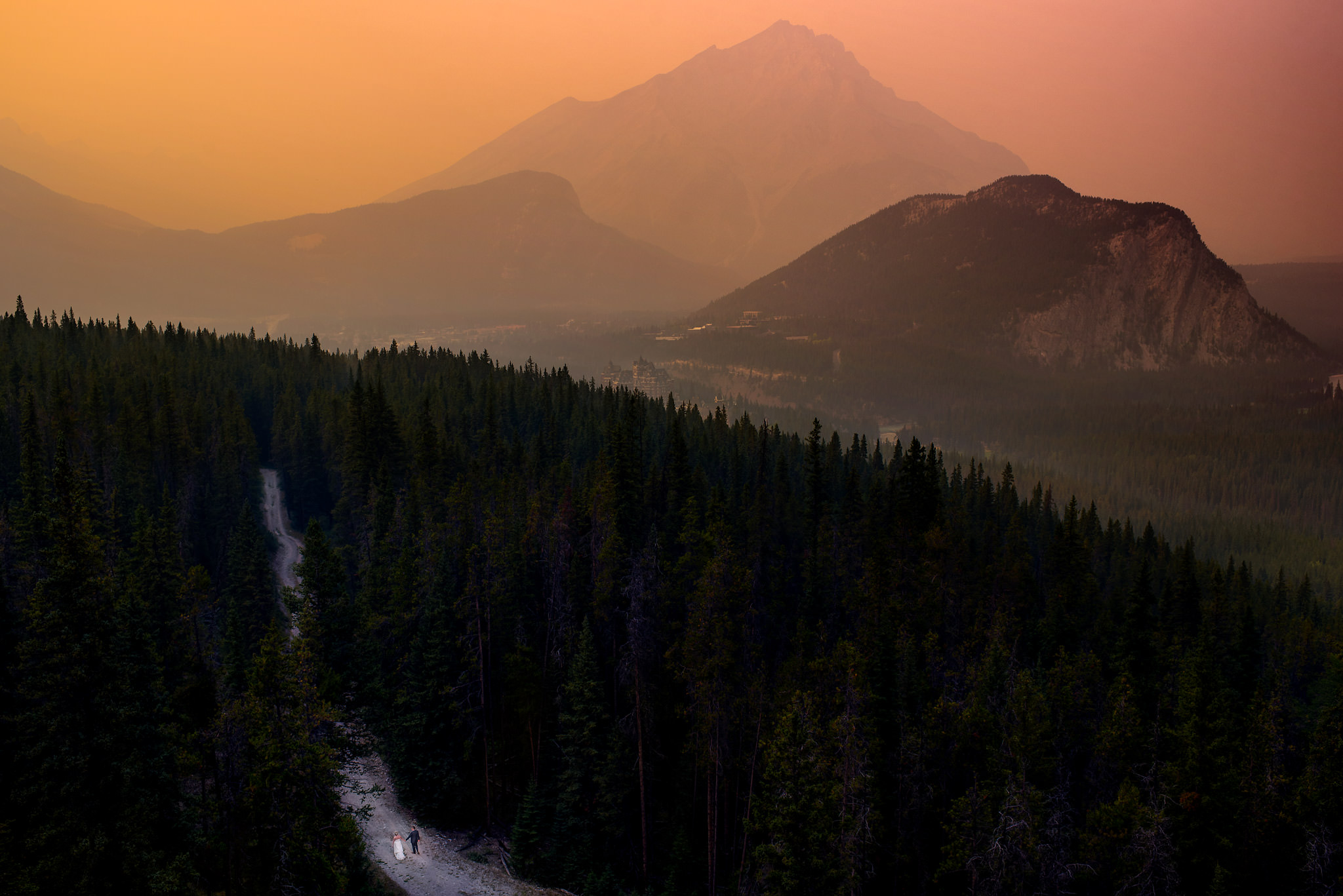 bride and groom walking in the mountains by Banff wedding photographer