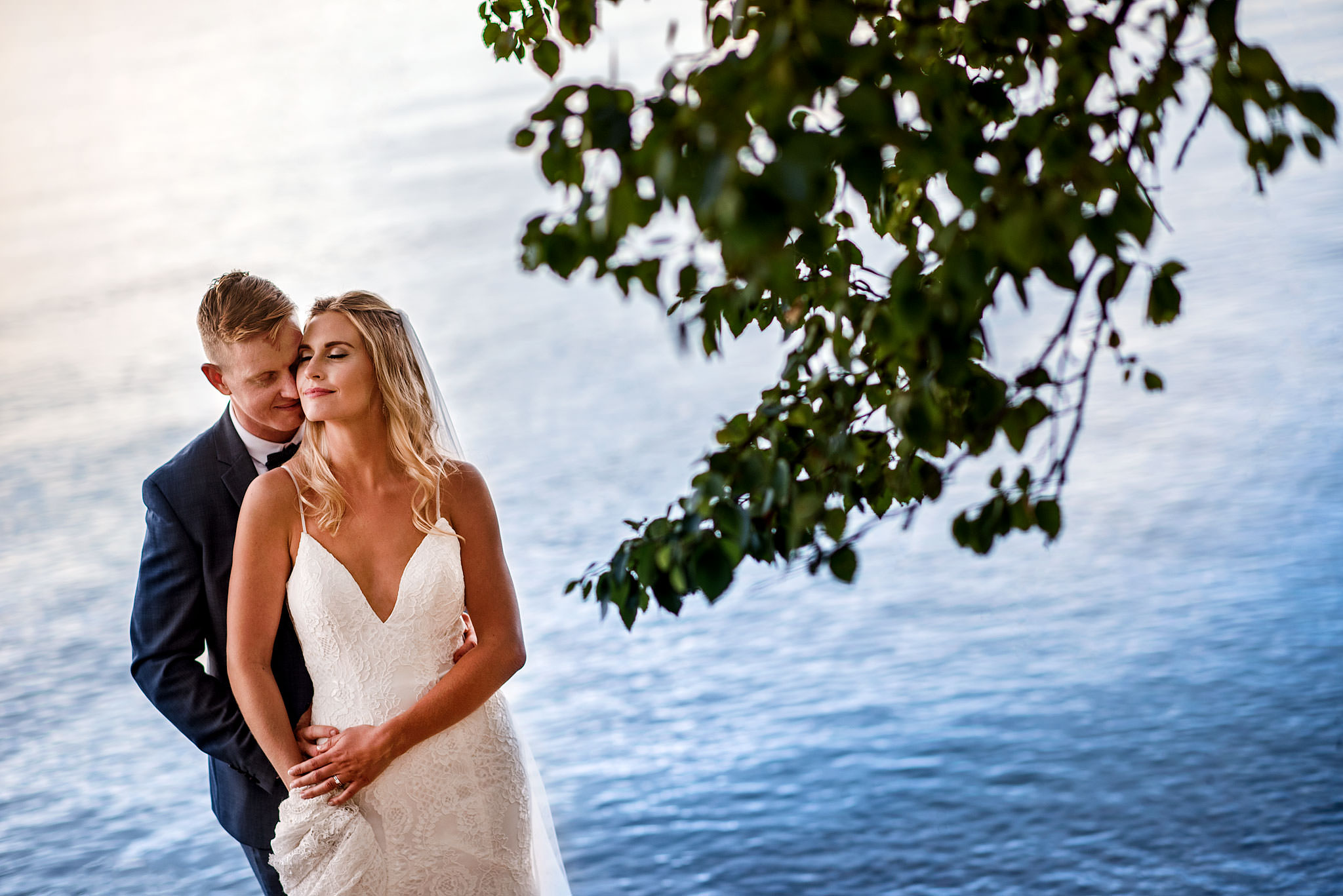bride and groom embracing in front of a lake by calgary wedding photography sean leblanc