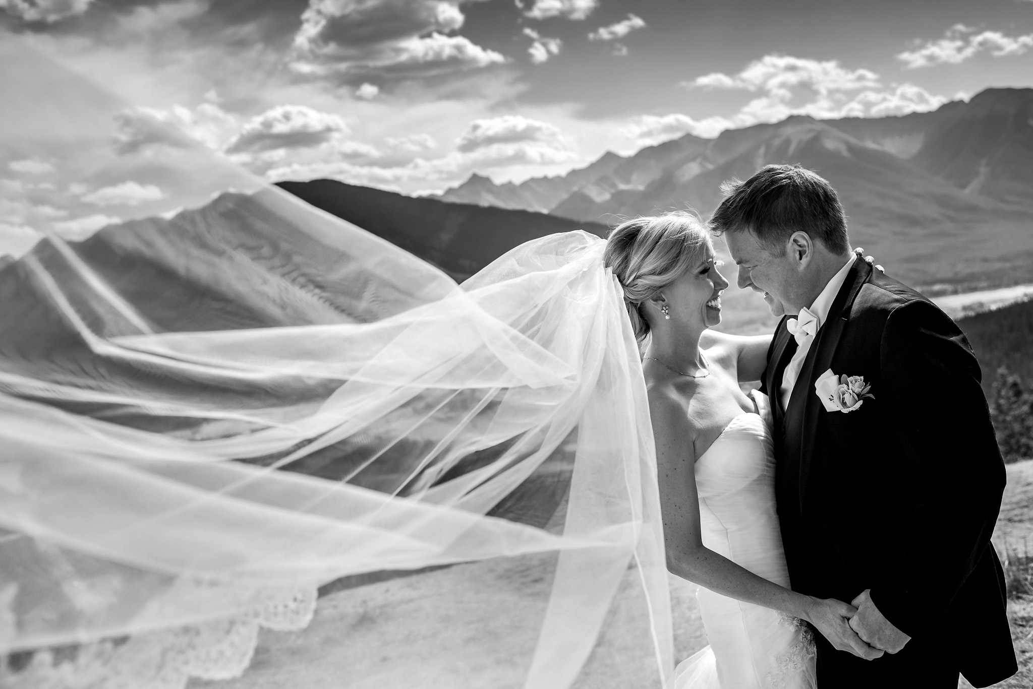 bride and groom smiling at each other with her veil flowing in the wind by calgary wedding photographer sean leblanc