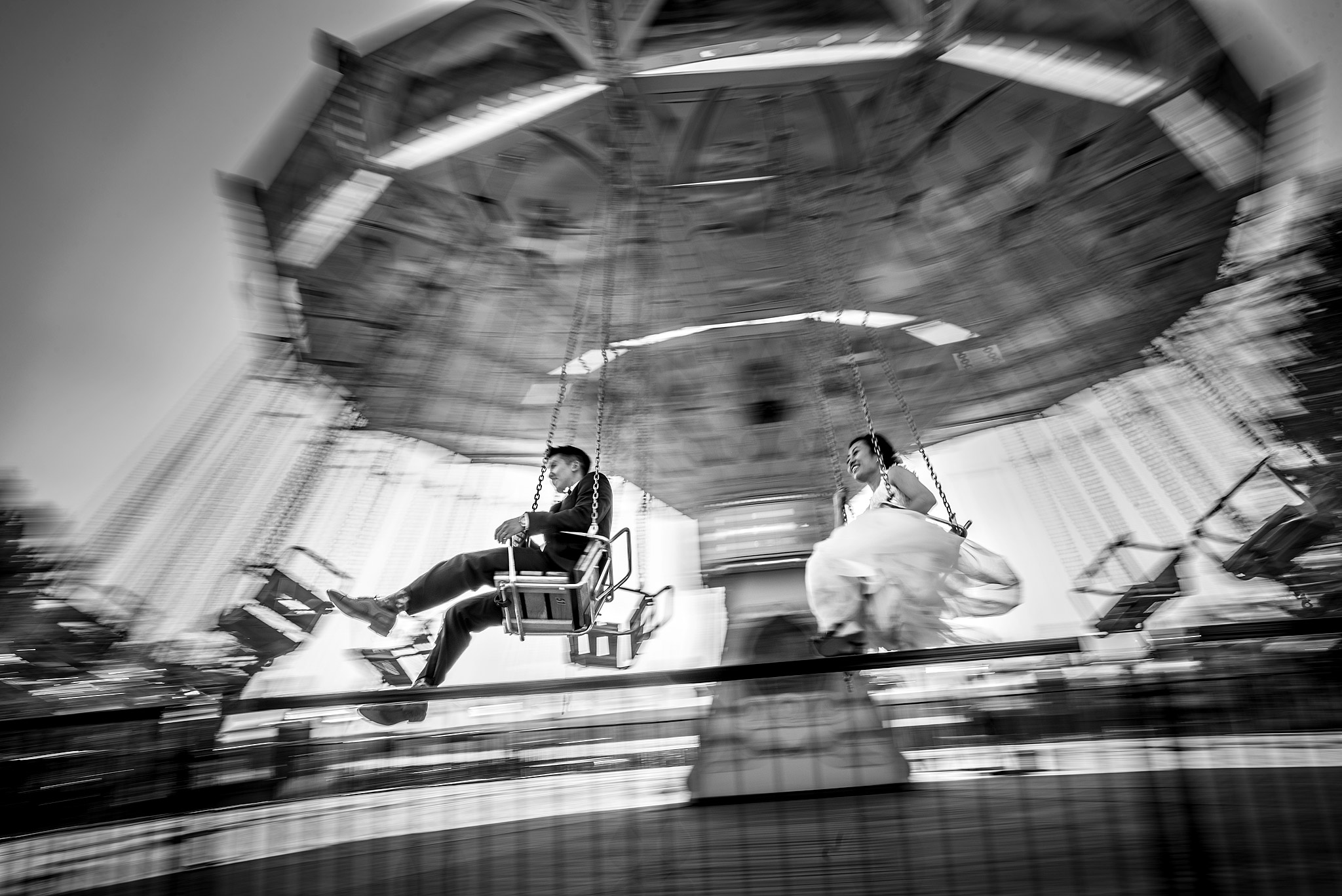 bride and groom spinning around on a ride by calgary wedding photographers