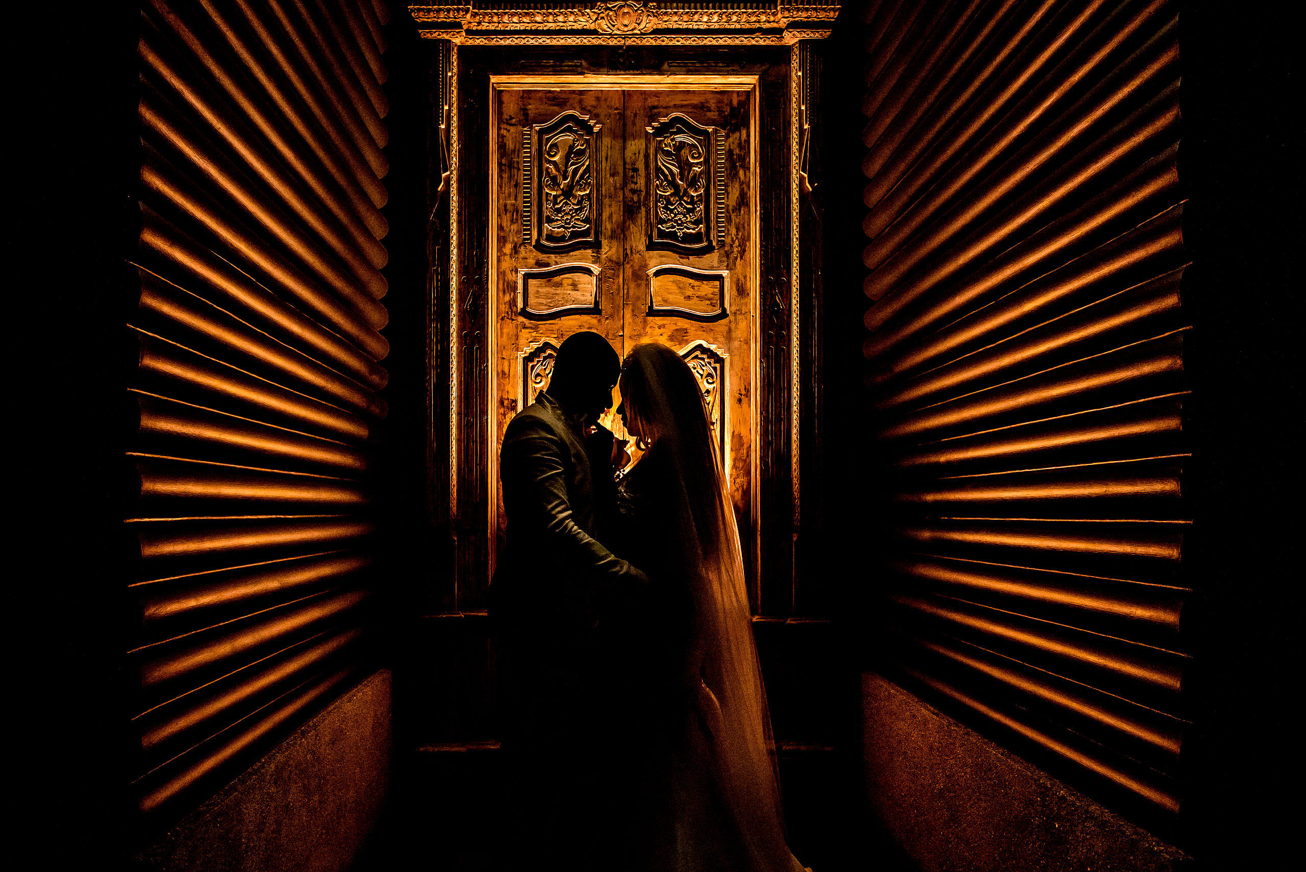 bride and groom silhouetted against a carved door