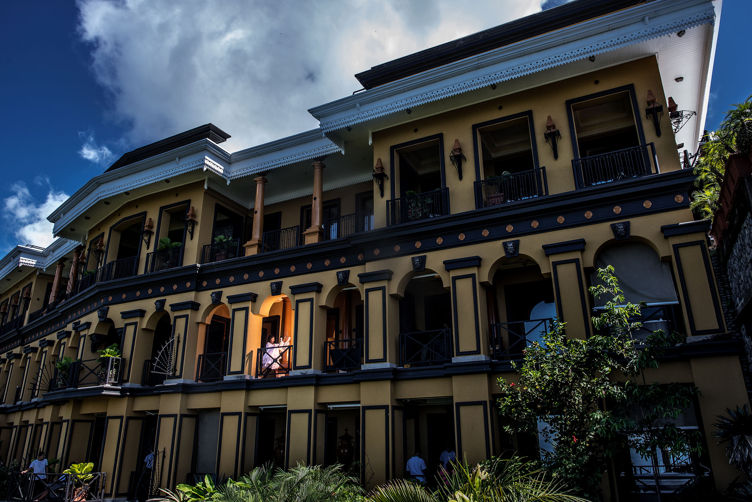 a bride walking with her dress on a balcony at Zephyr Palace Destination Wedding in Costa Rica by Sean LeBlanc