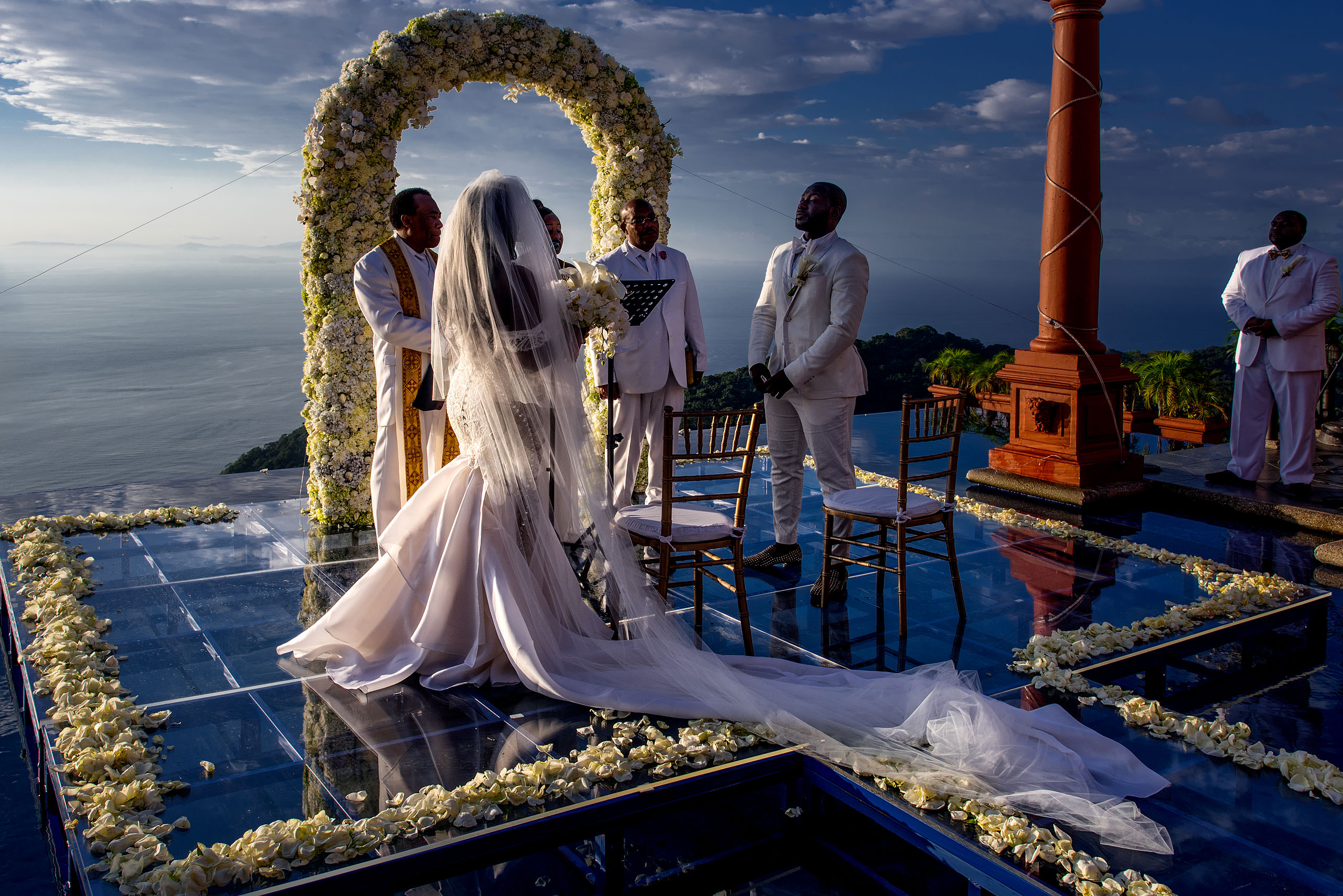 a bride with a long dress looking at groom in front of the ocean at Zephyr Palace Destination Wedding in Costa Rica by Sean LeBlanc