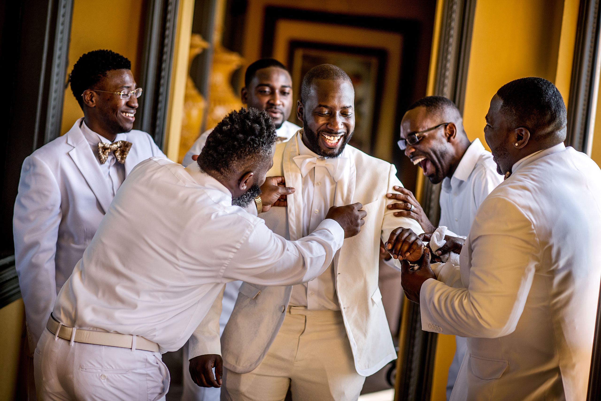 groomsmen joking around while getting ready for a wedding by destination wedding photographer