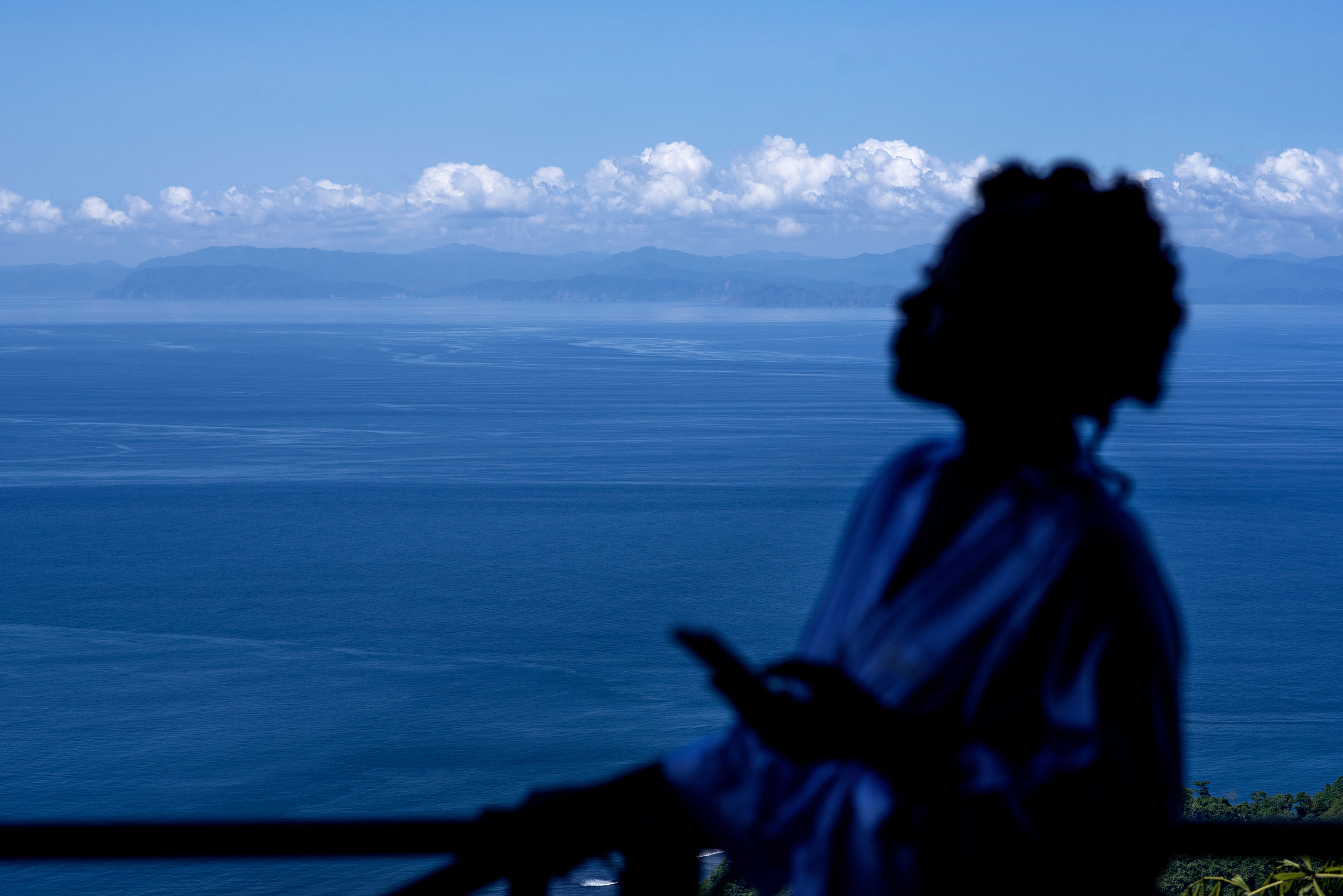 a women standing on a balcony overlooking the ocean at Zephyr Palace Destination Wedding in Costa Rica by Sean LeBlanc