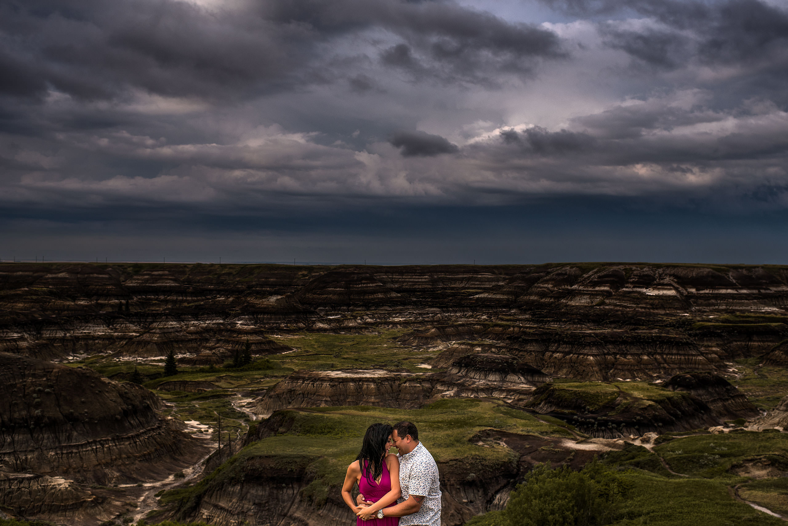 a man embracing his fiancé infront of a canyon - drumheller engagement session
