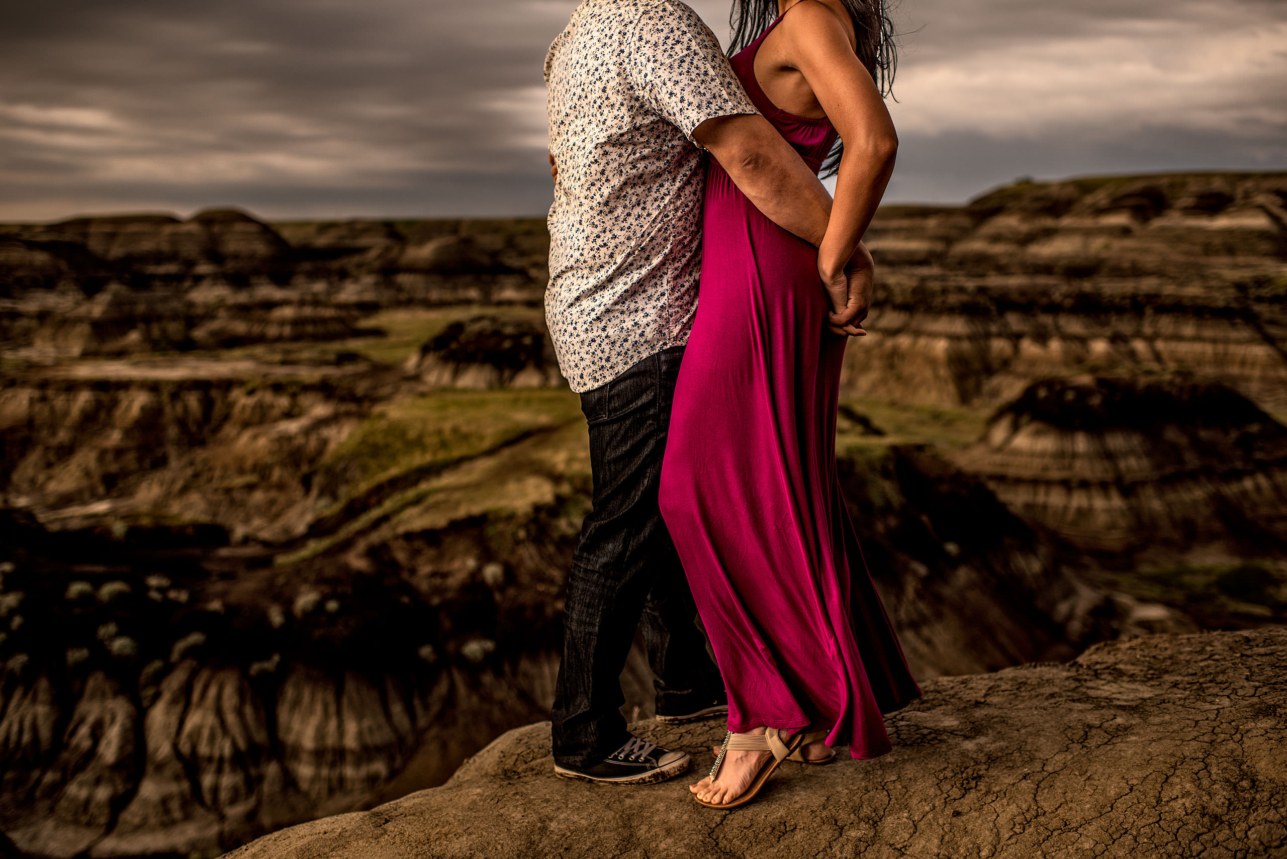 a man holding his fiancé's hand behind her back while standing in front of a canyon - drumheller engagement session