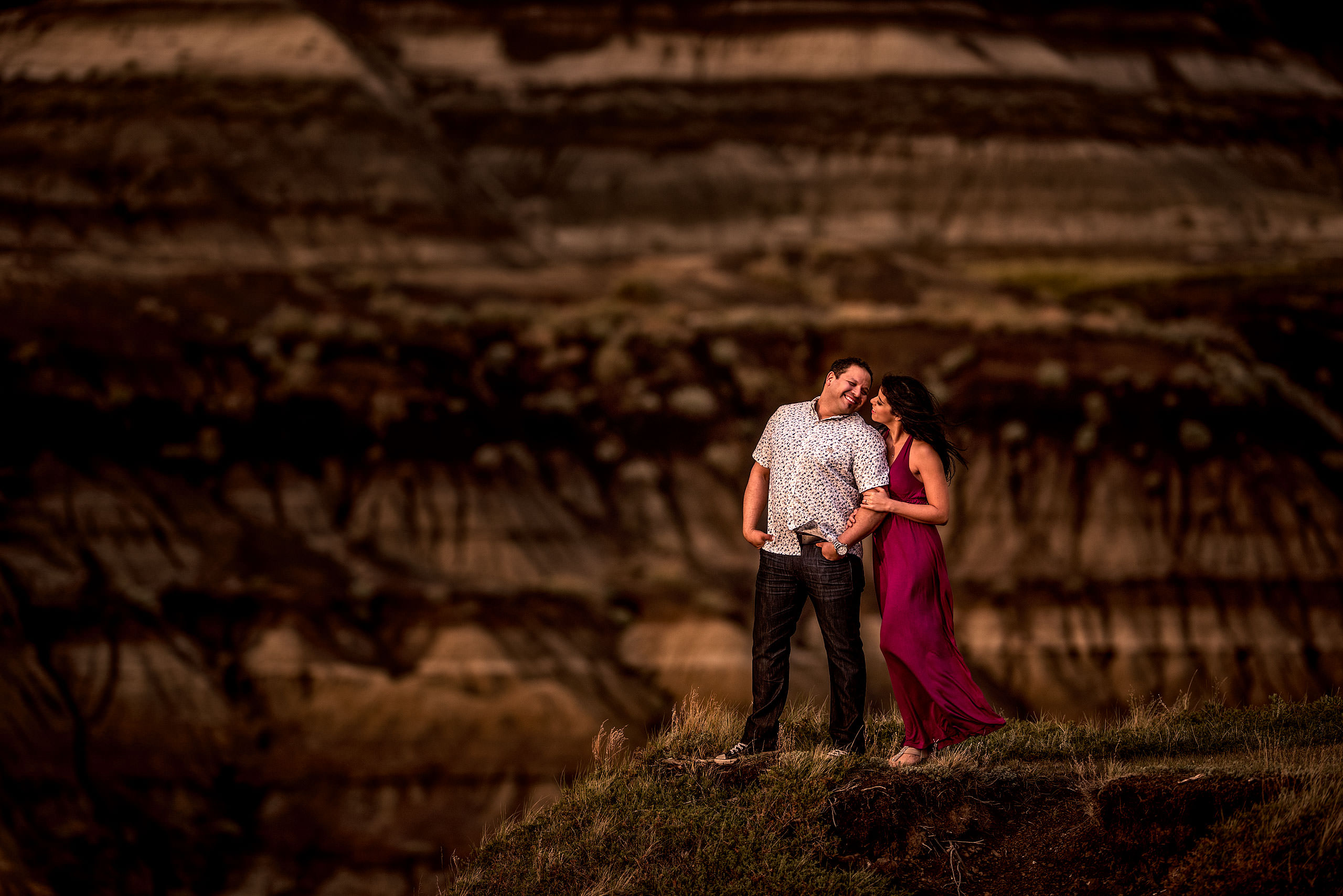 a man leaning back to tell his fiancé something while standing in a canyon - drumheller engagement session