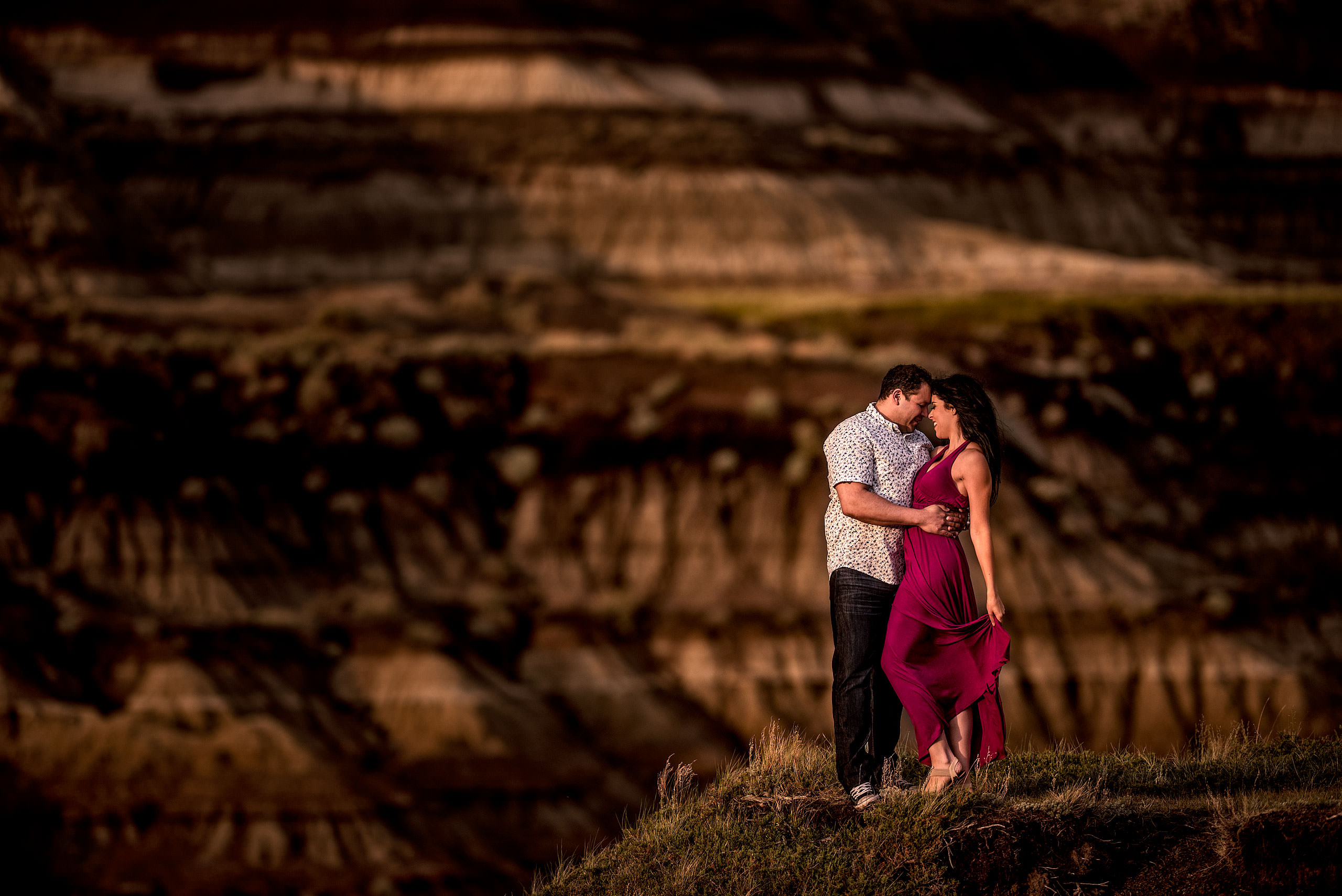 a man holding his fiancé close while she flips back her pink dress while standing in a canyon - drumheller engagement session