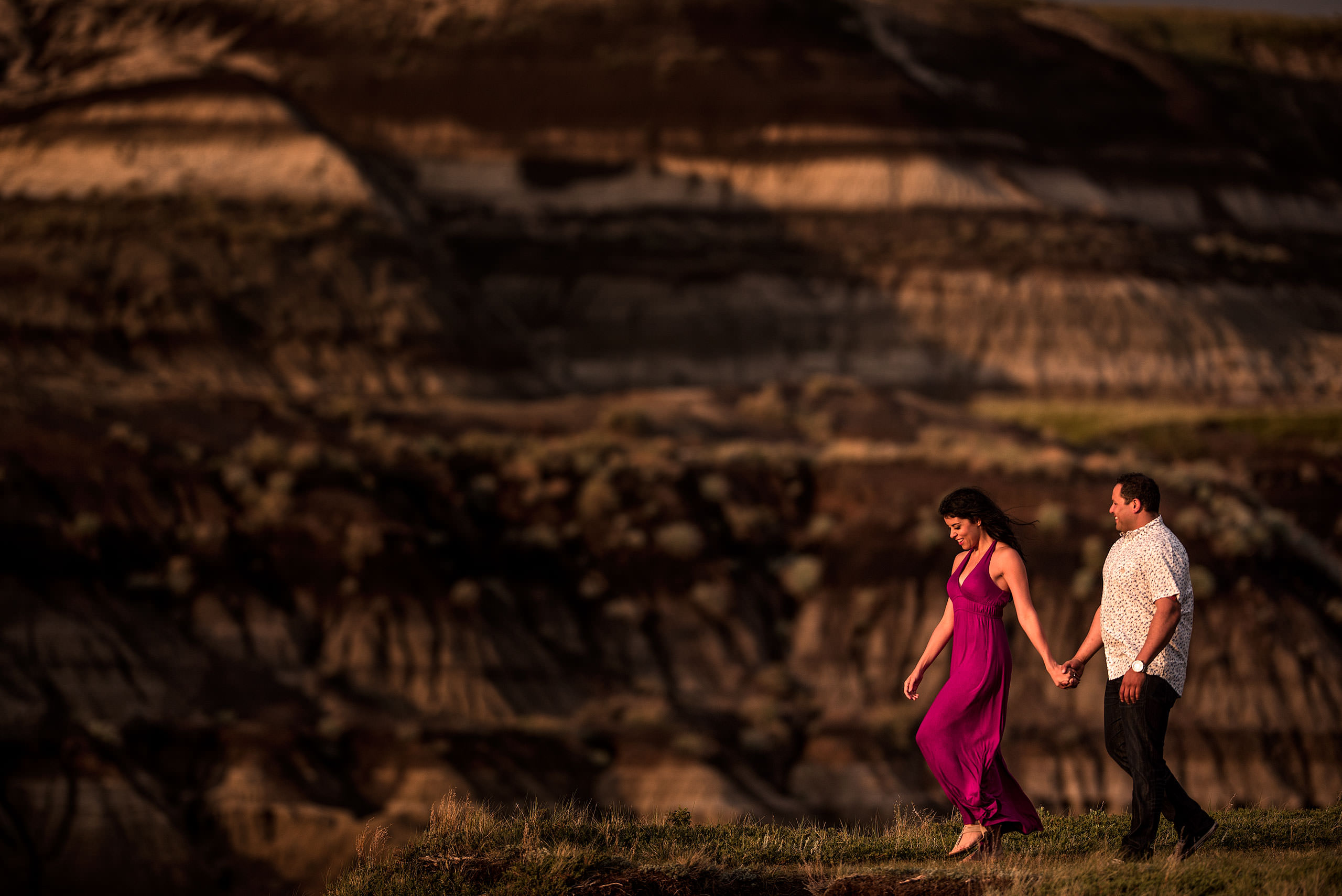 a women wearing a pink dress walking with her fiancé in a canyon - drumheller engagement session