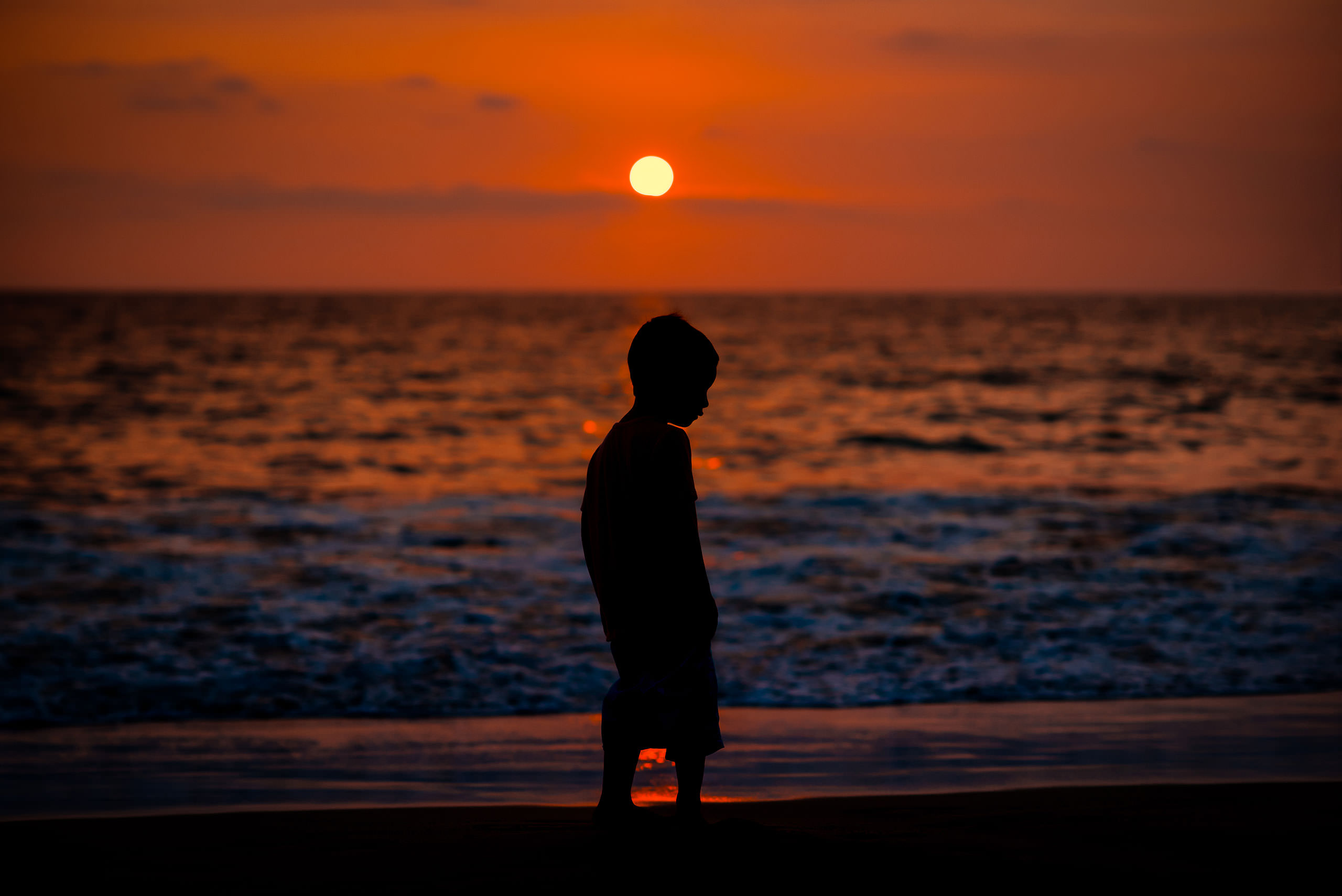 young boy on a Hawaiian beach at sunset silhouetted against the ocean by destination family photographers sean leblanc